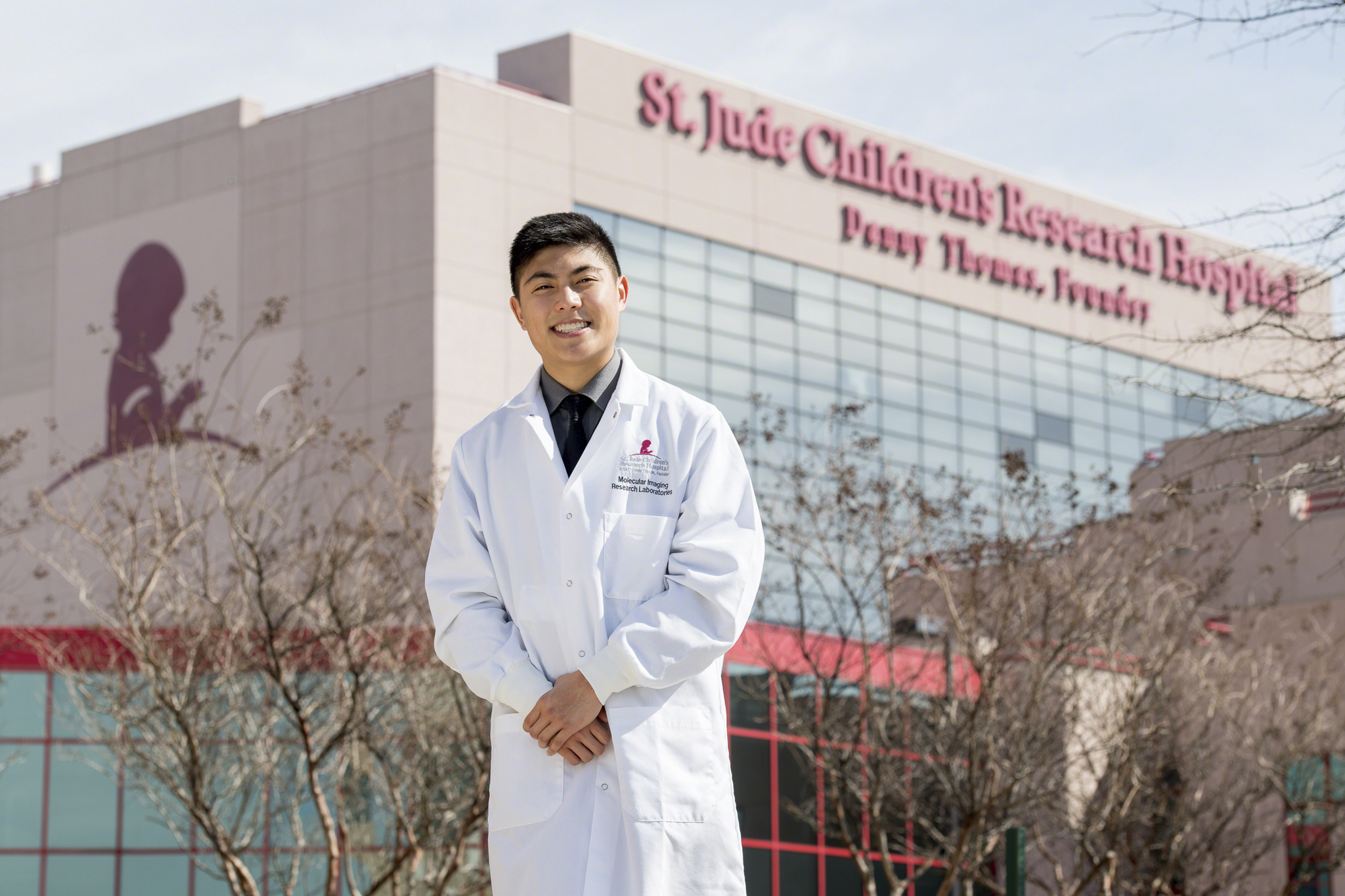 A young man in a white coat stands outside St. Jude Children's Research Hospital.