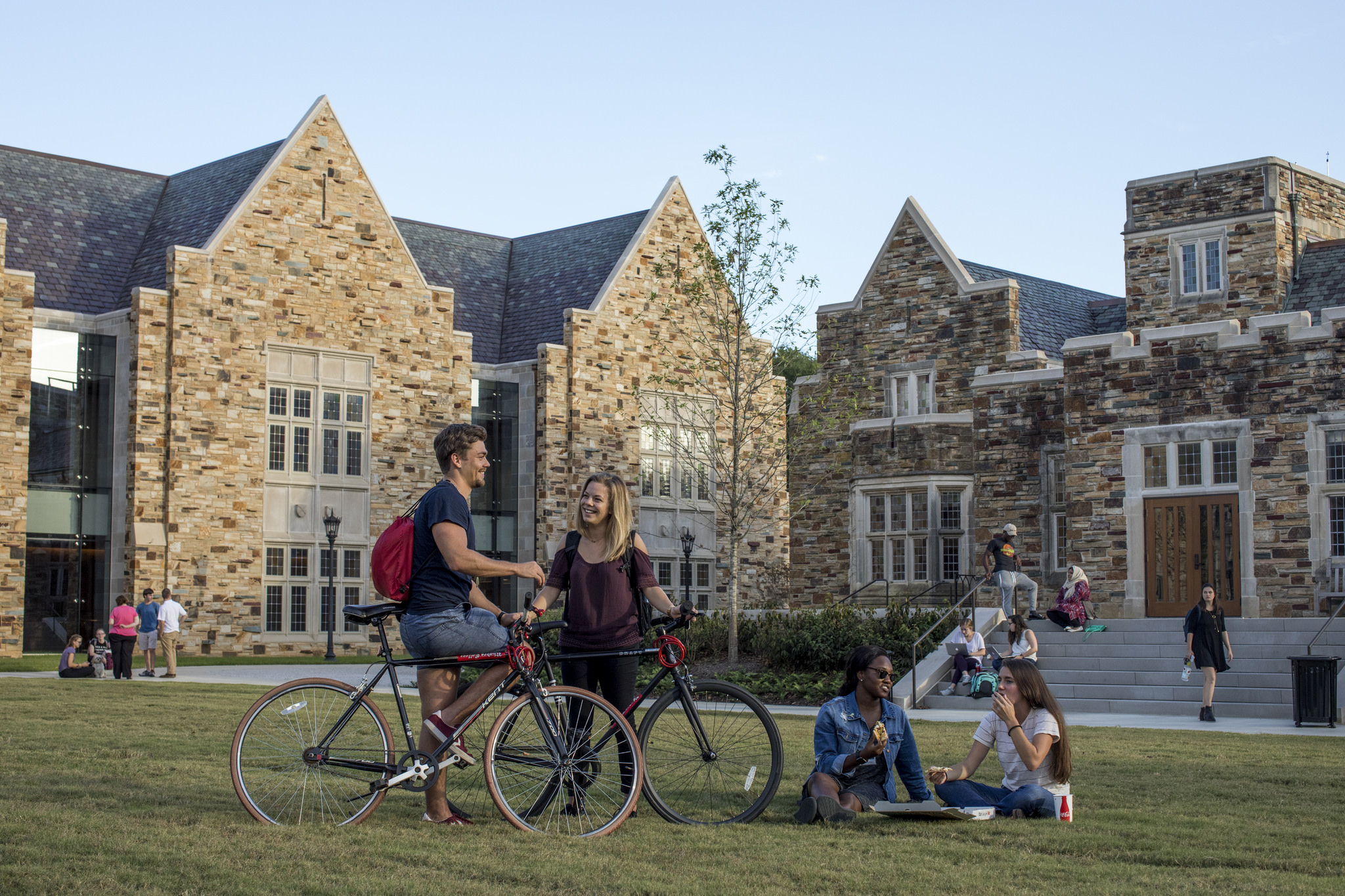 Students meet at sunset on a grassy quad surrounded by beautiful stone buildings.