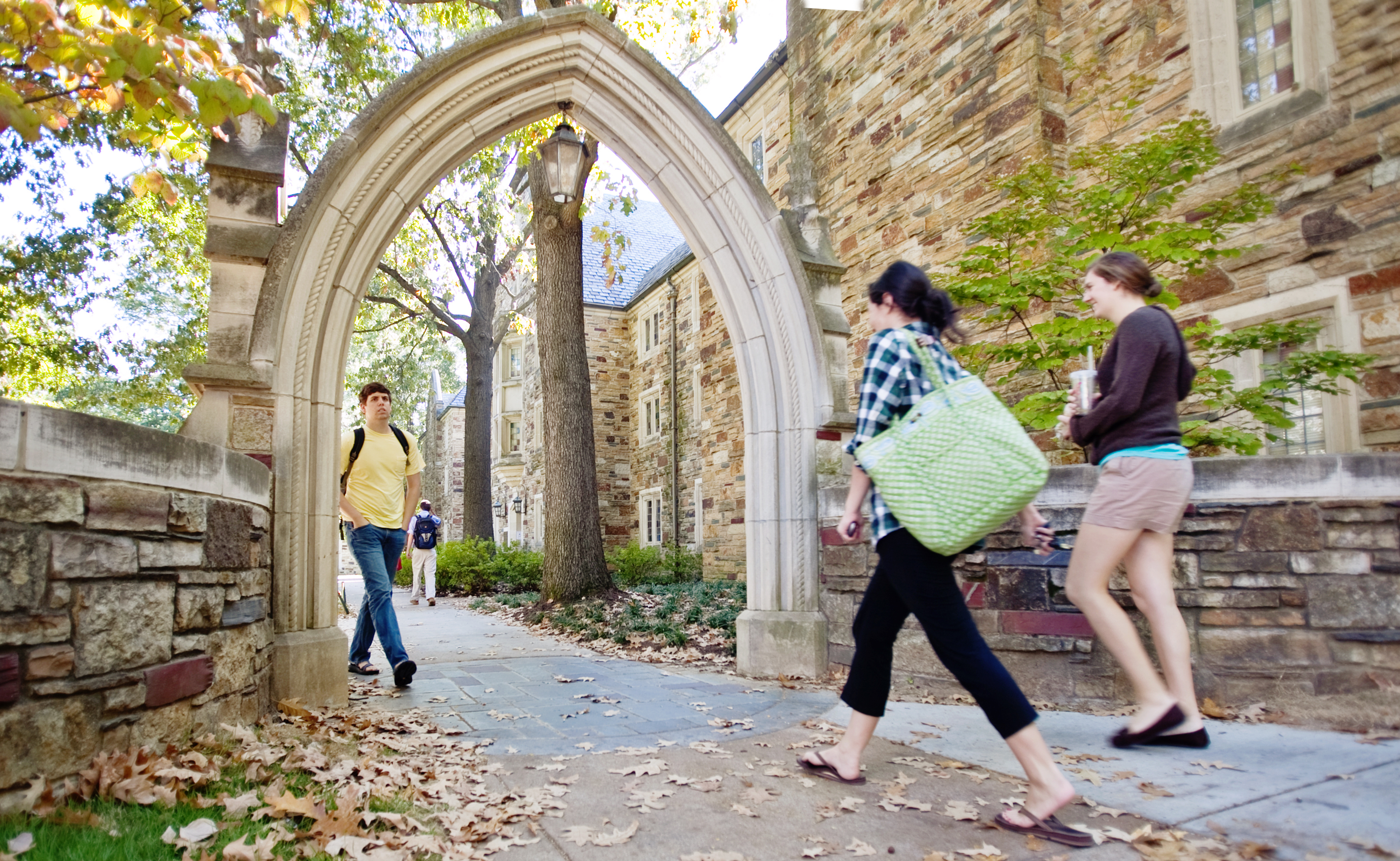 Students walking under an arch.