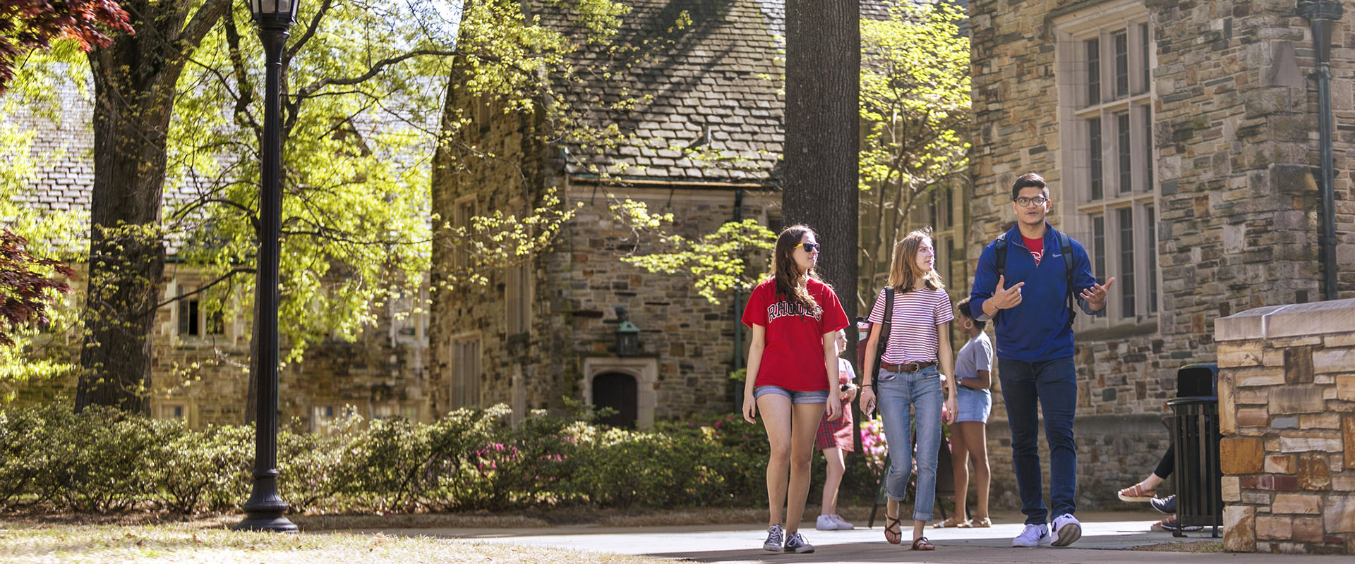 Three students walk by a fieldstone building with trees