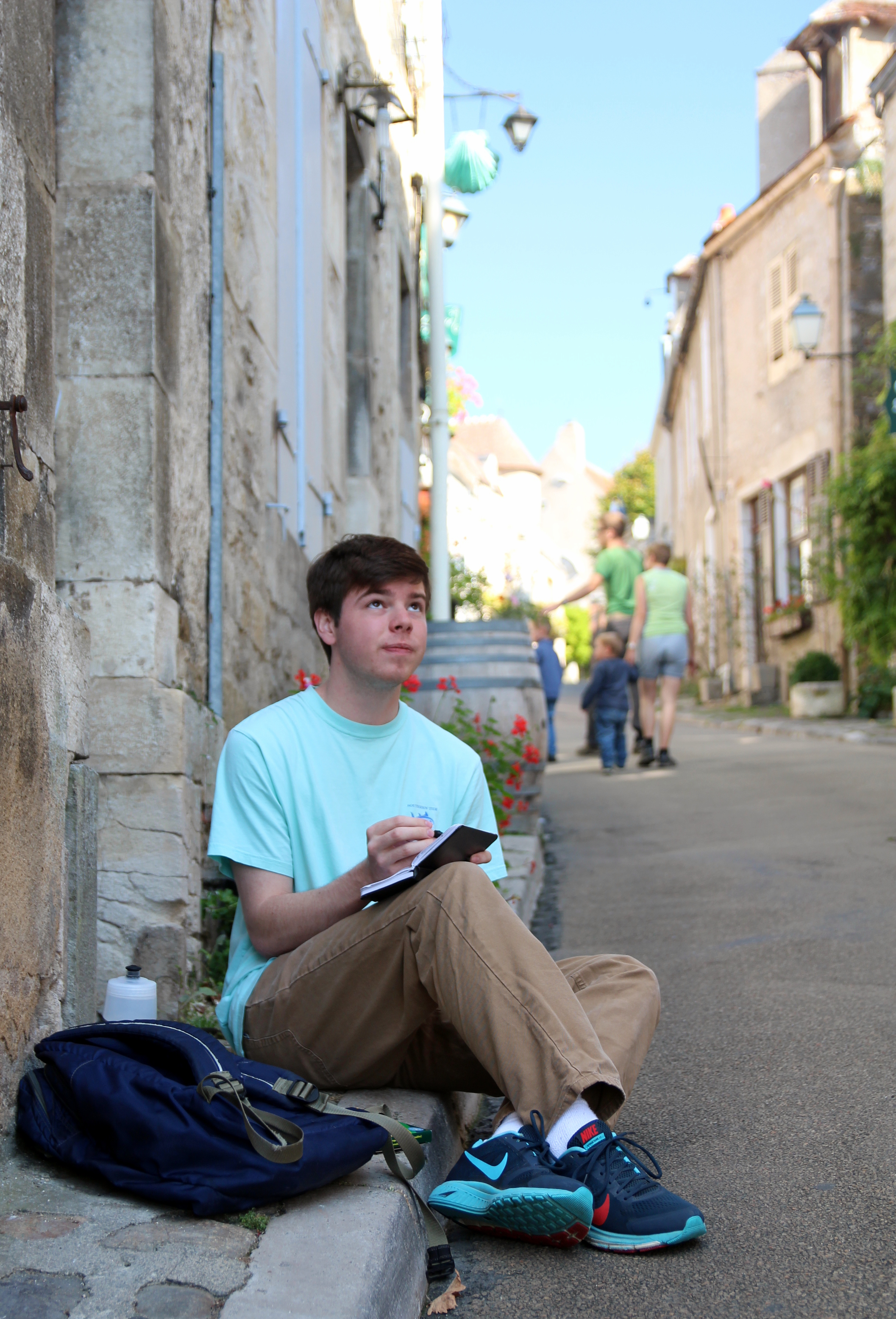 A student sits on the curb of a European street sketching in his notebook