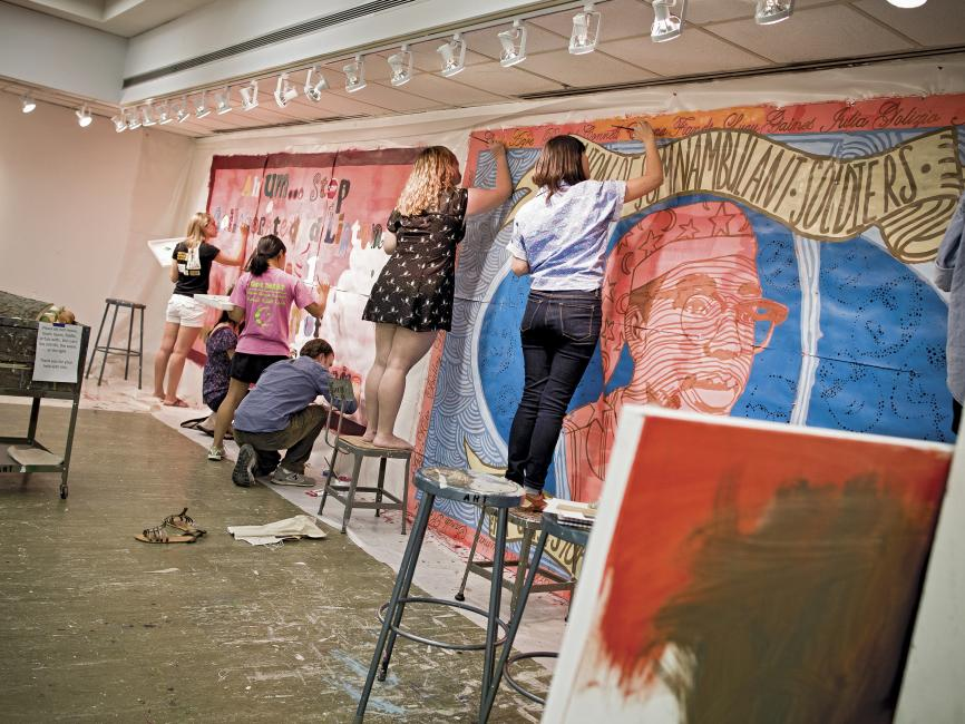 Students paint a mural on an interior wall