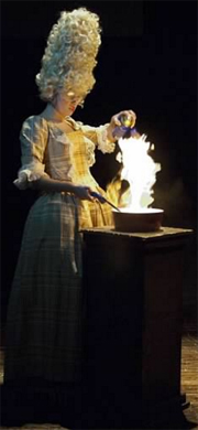 A woman in an 18th century dress and wig makes fire in a pan on a pedestal