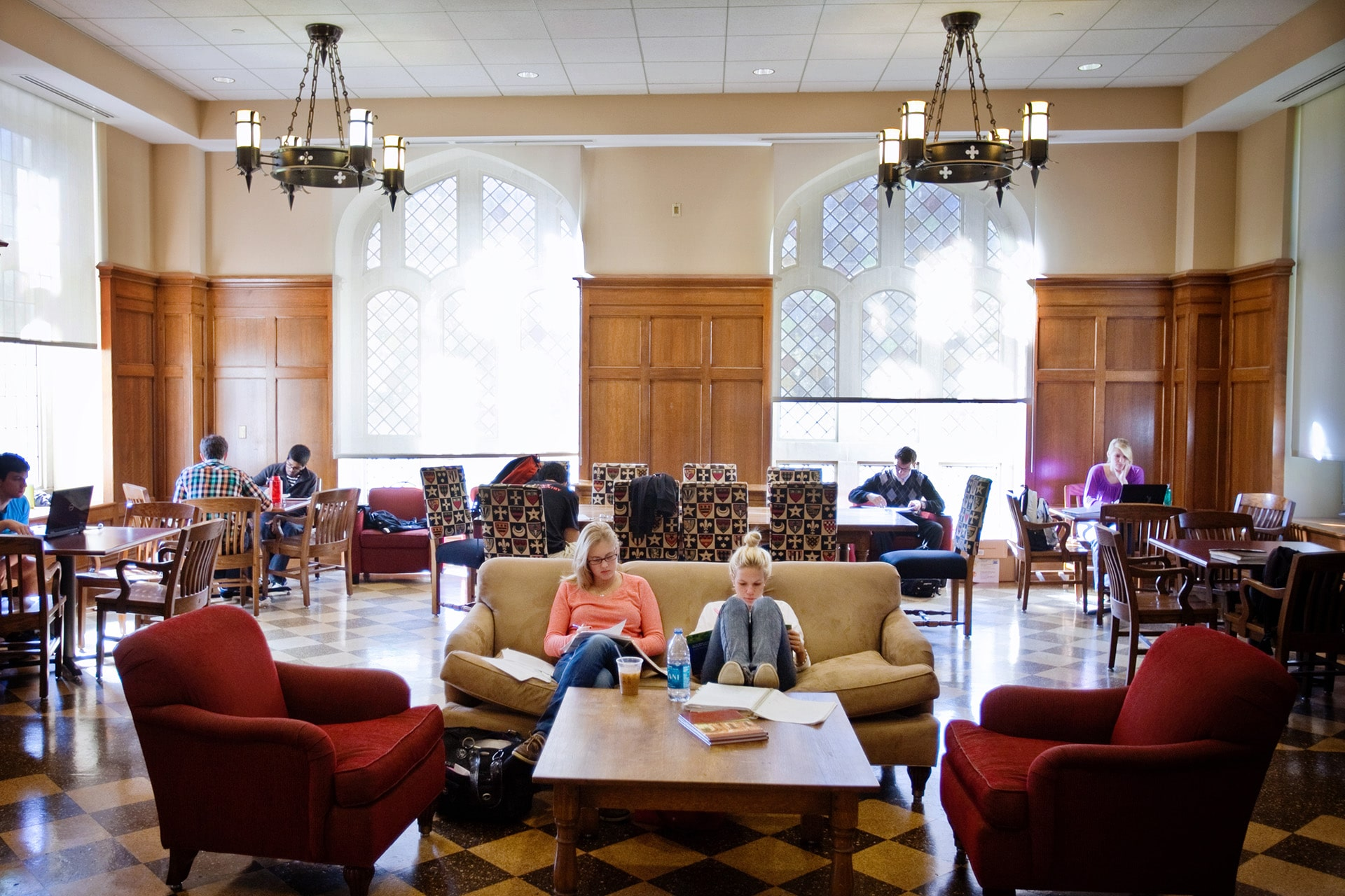 Students studying in a large, bustling common room next to a coffee stand.