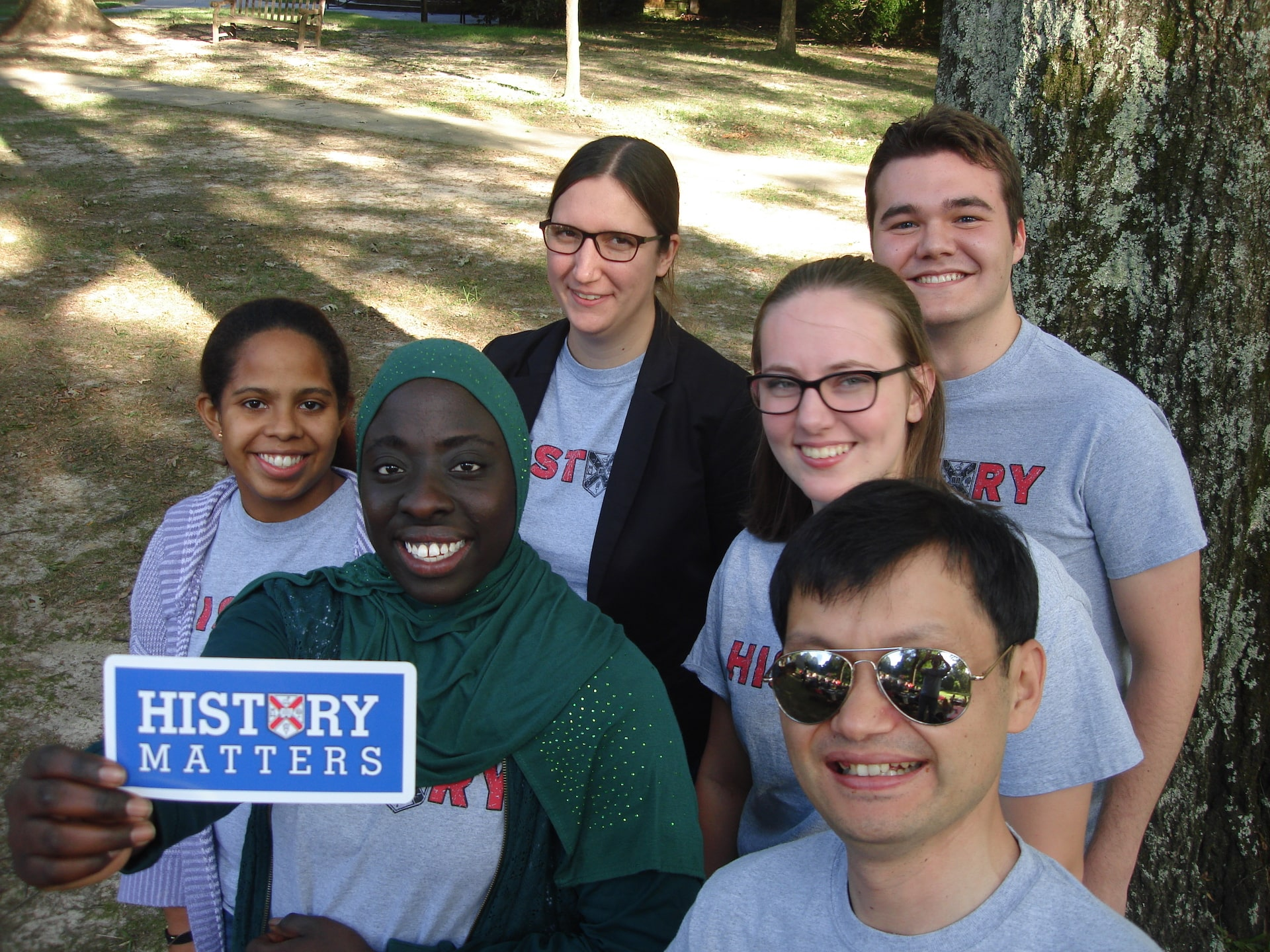 "A group of four students and a professor with a ""History Matters"" sign."