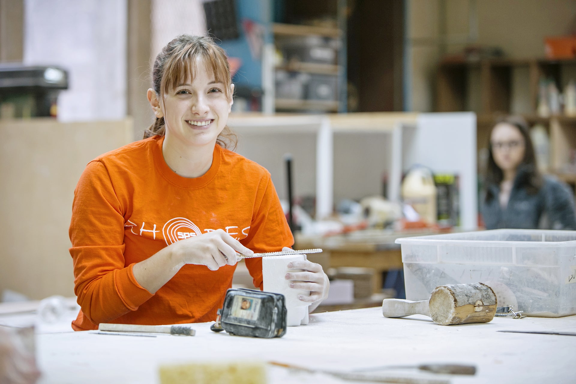 A young woman in an orange shirt files down the end of a mold.