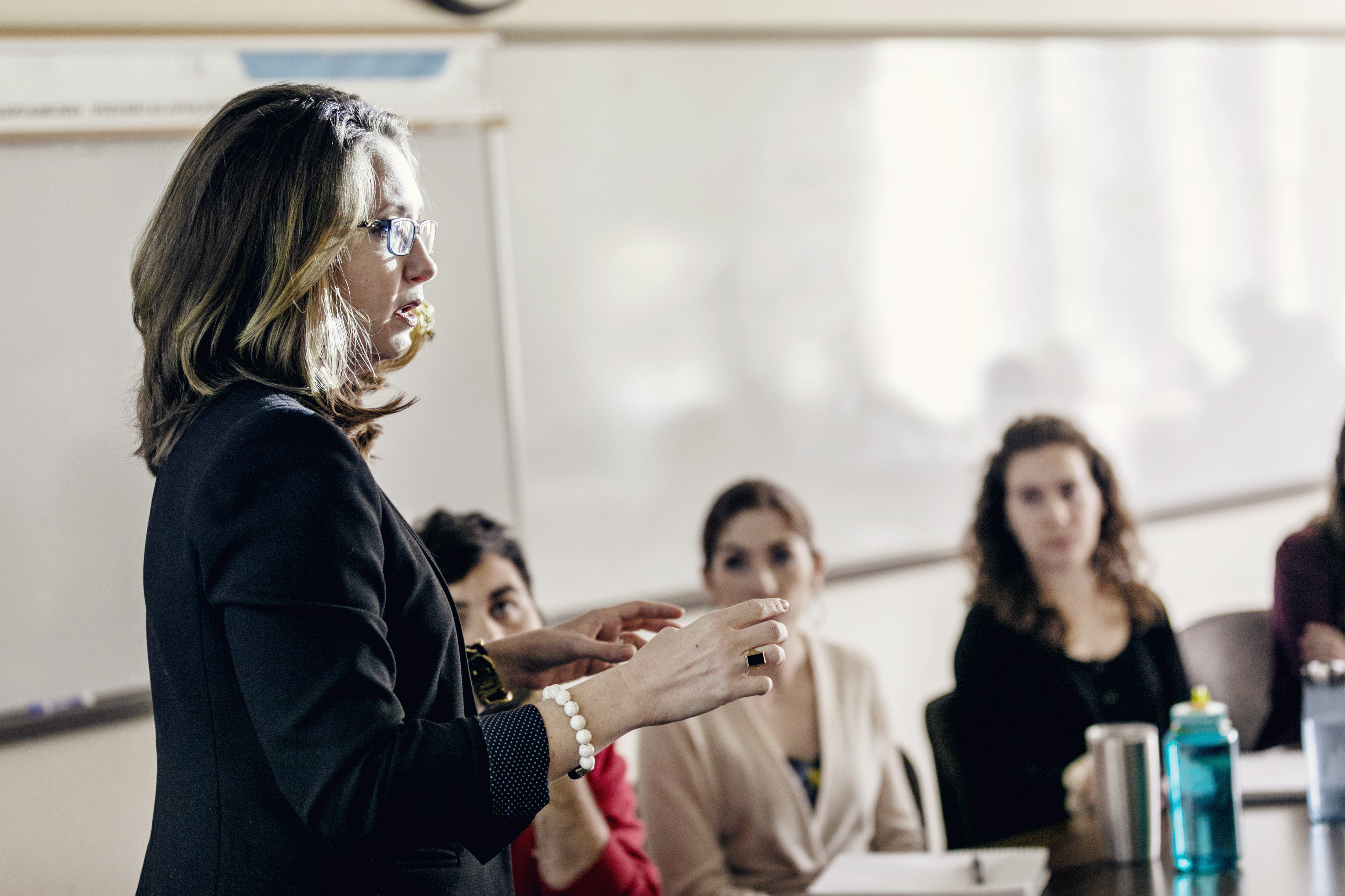 A professor, seen in profile, speaks to her assembled class.