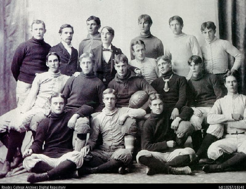 A black and white photo of a group of men in 19th century football attire