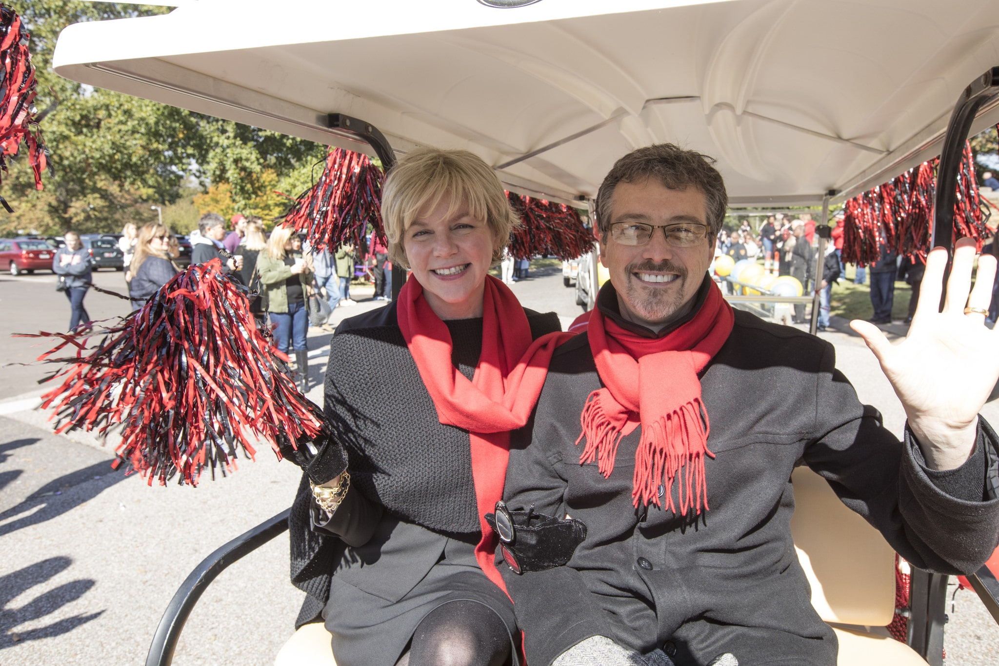 President and Dr. Hass riding in a golf cart, sporting red scarves and waving red and black moms