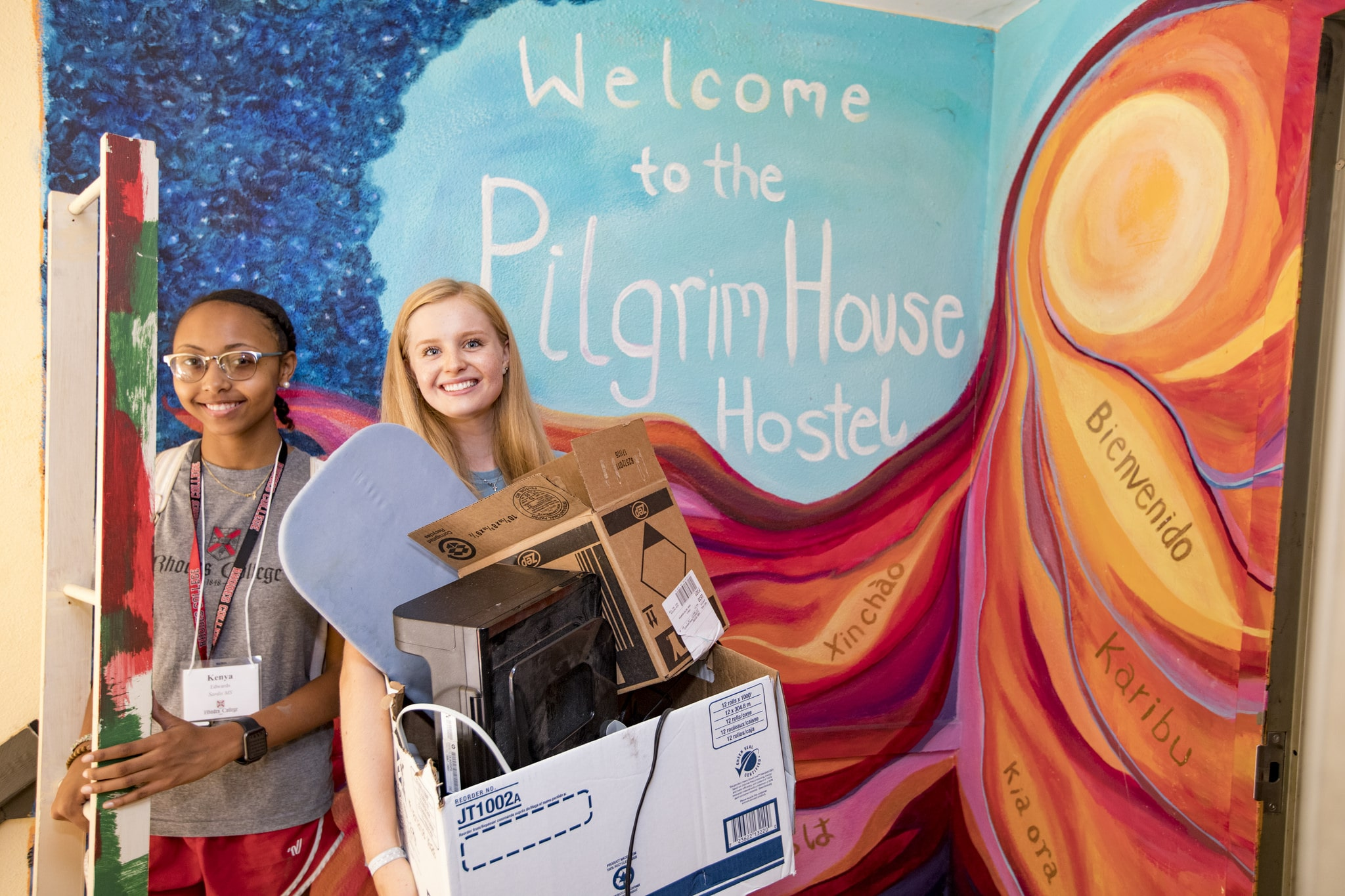 "Two students carrying boxes in front of a mural that reads ""Pilgrim House Hostel"""