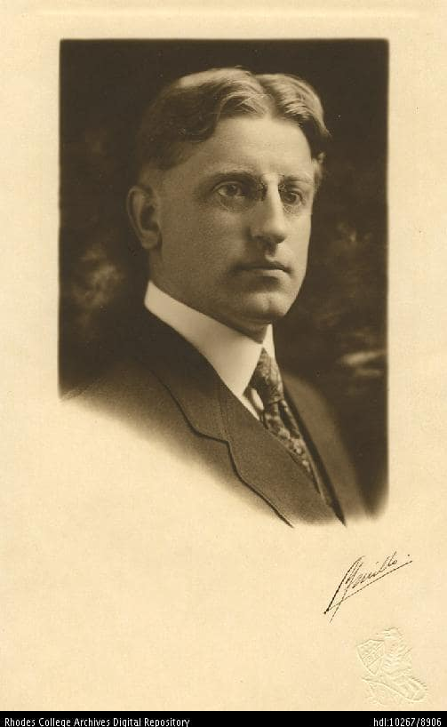 A portrait of a man rocking the middle part in the 20s, wearing a suit and pince nez glasses.