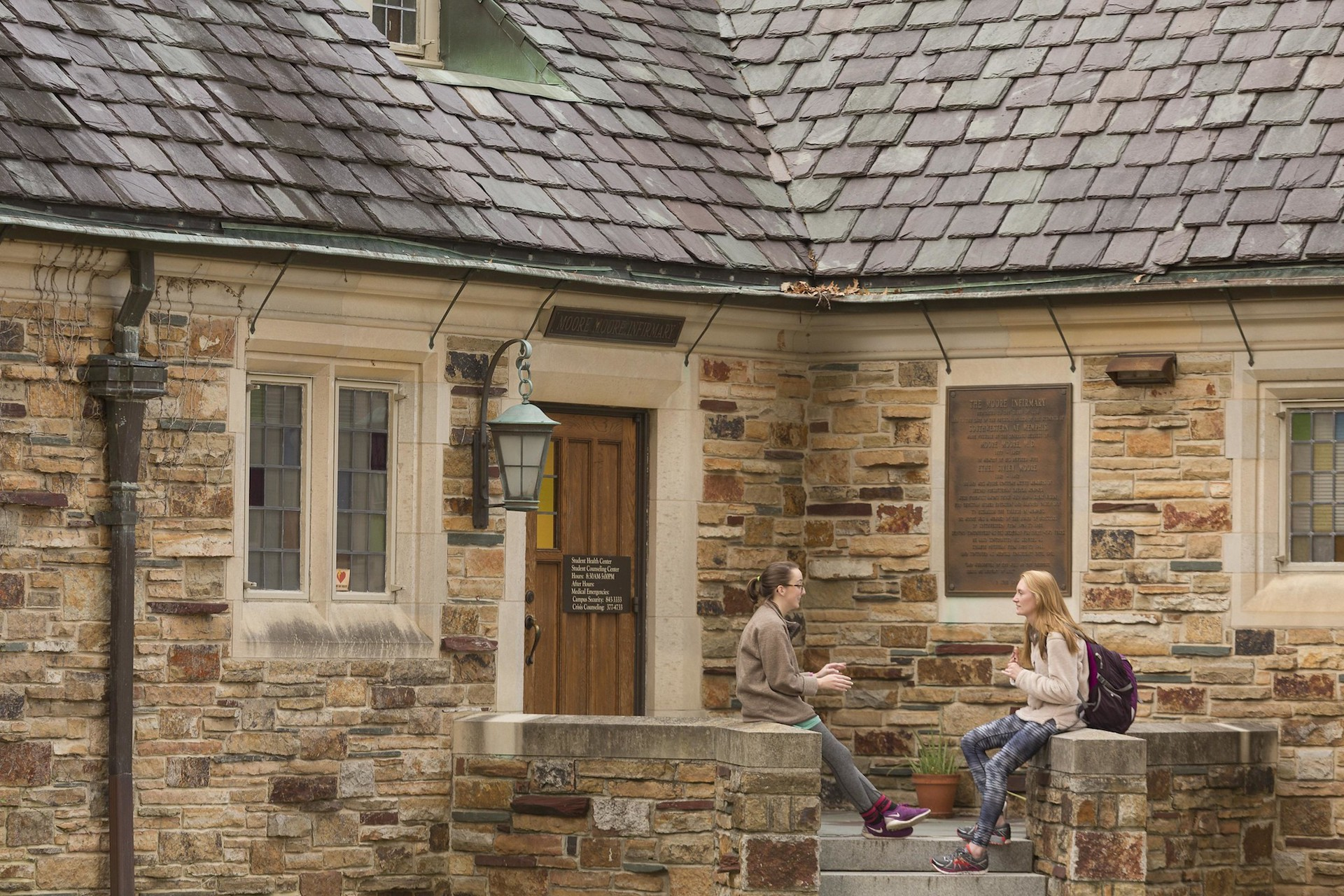 Two girls sitting in front of a sandstone building with a slate roof.