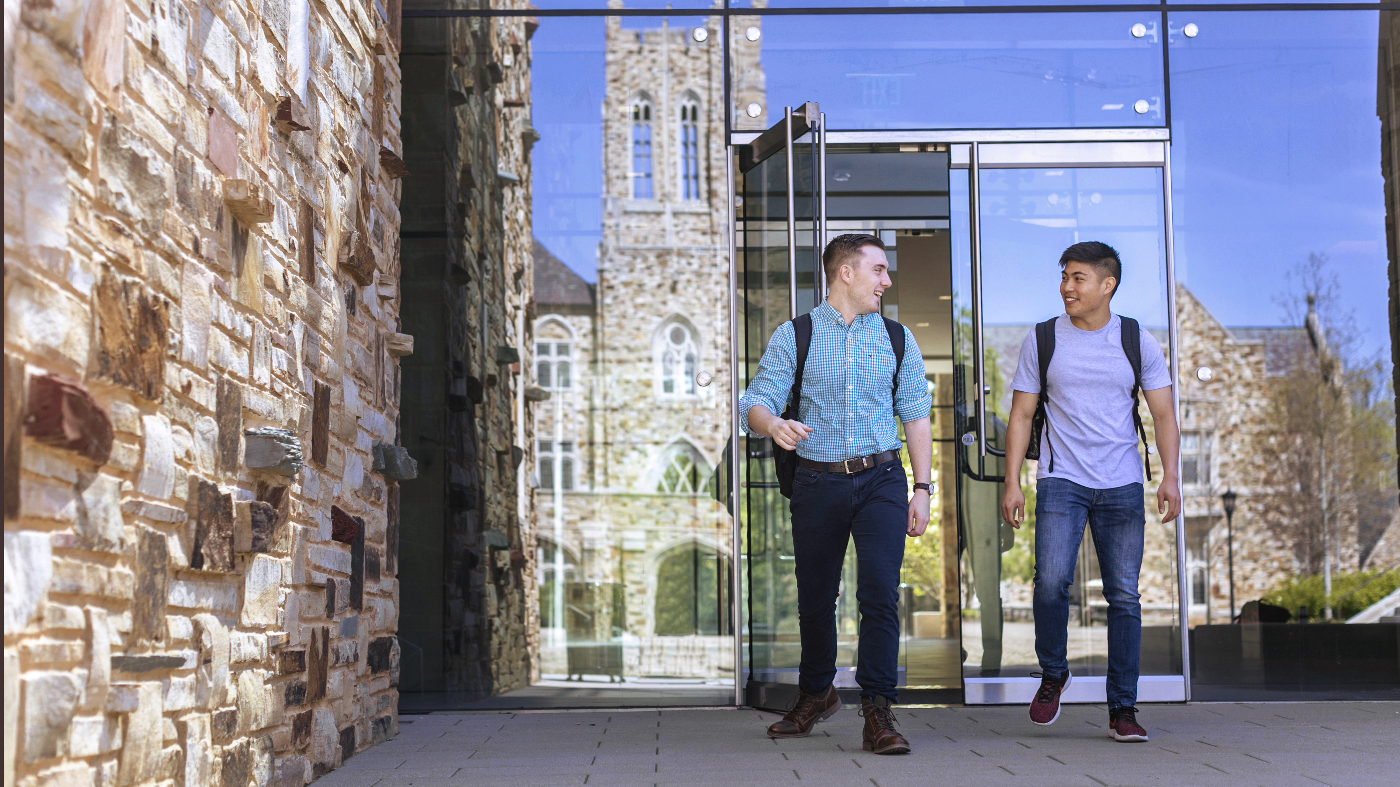two students walk outside Robertson Hall