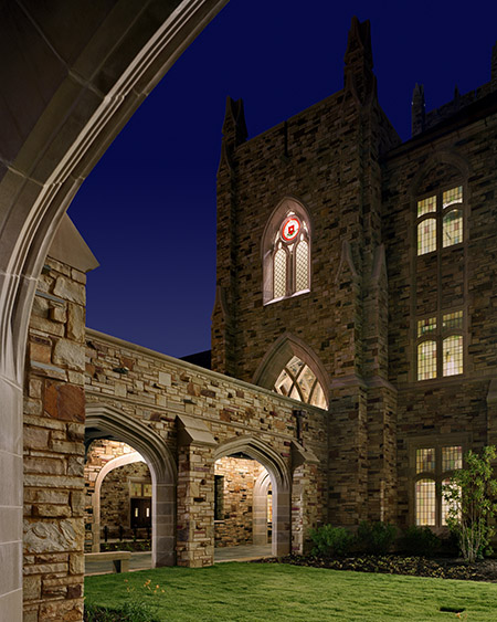 a night shot of the Paul Barret, Jr. Library cloister, a gothic building made of sandstone