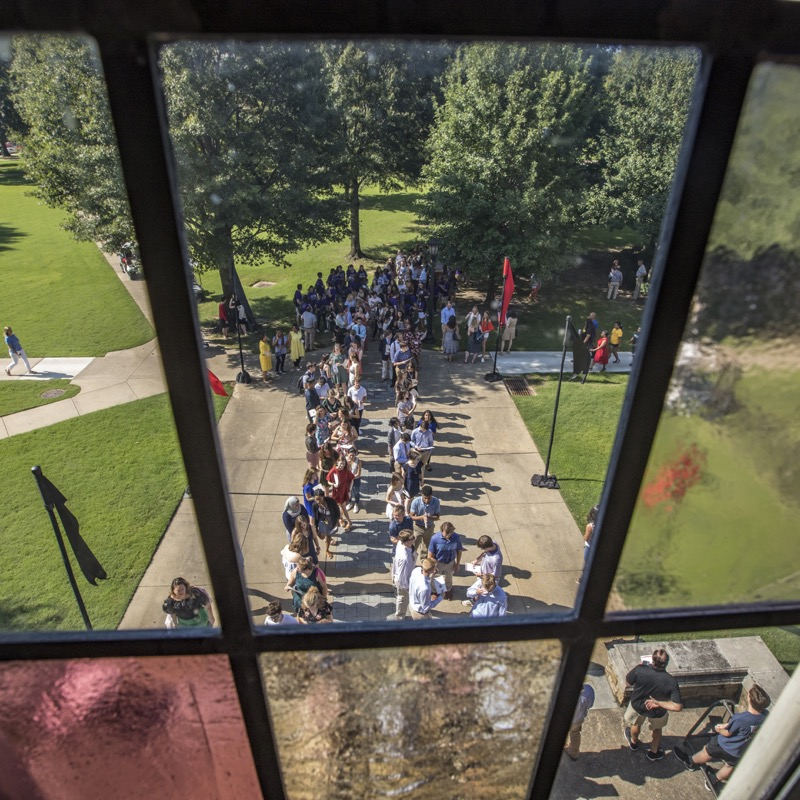 Students lined up in the quad as seen through a stained glass window.
