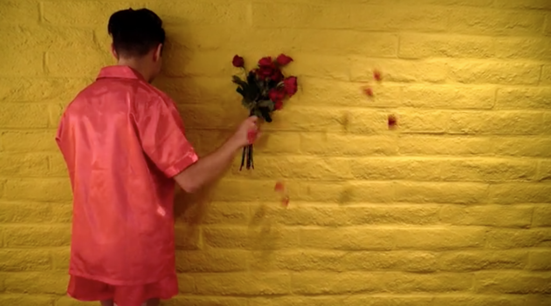 a  figure in a red shirt faces a yellow wall and holds a bouquet against the wall