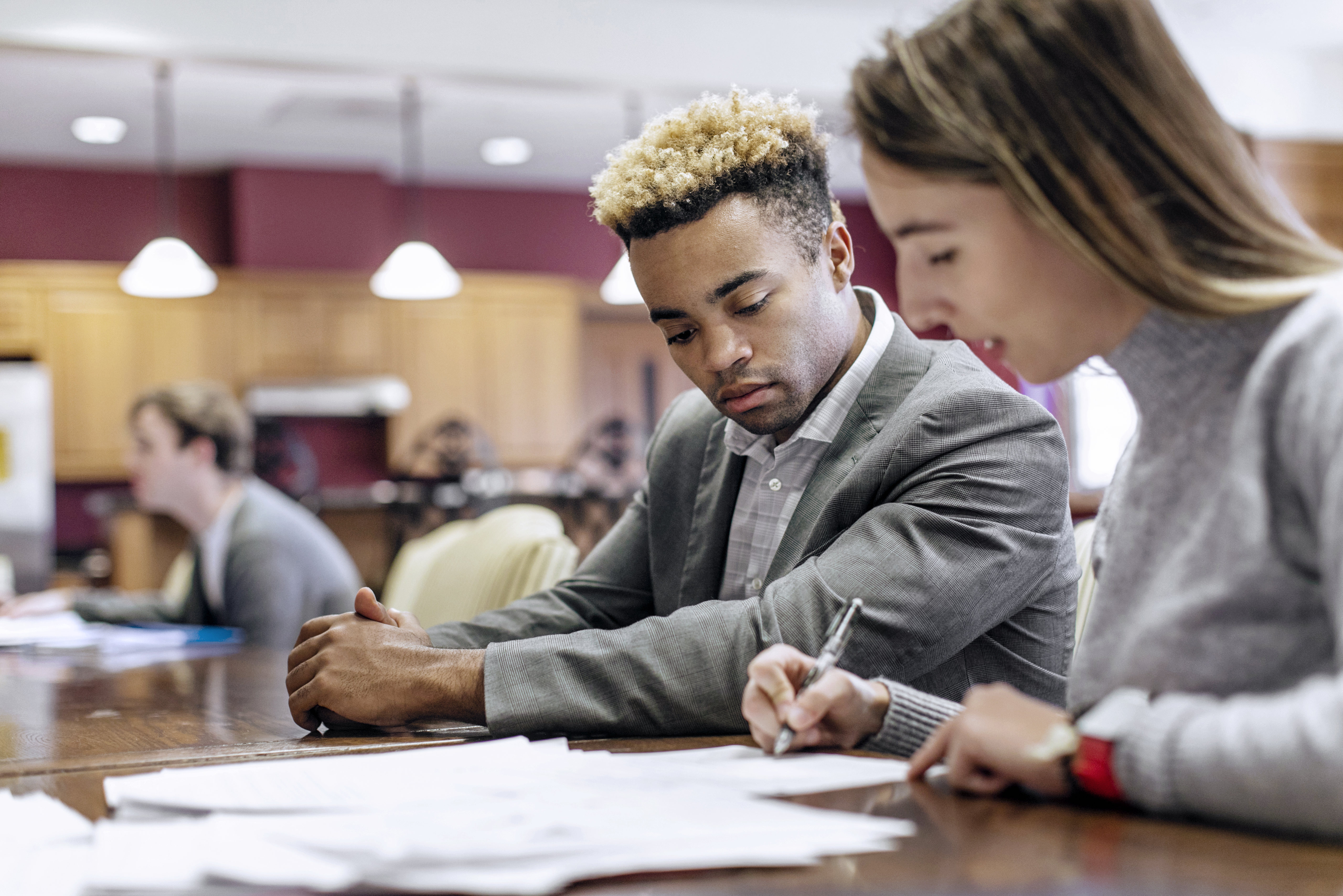 a male and female student look over some papers