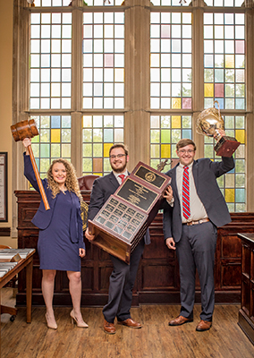 three students hold up trophies