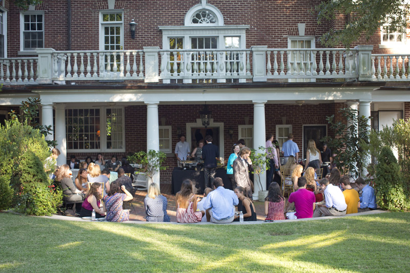 Students gather on the back patio of a red brick Georgian house with columns and a large lawn