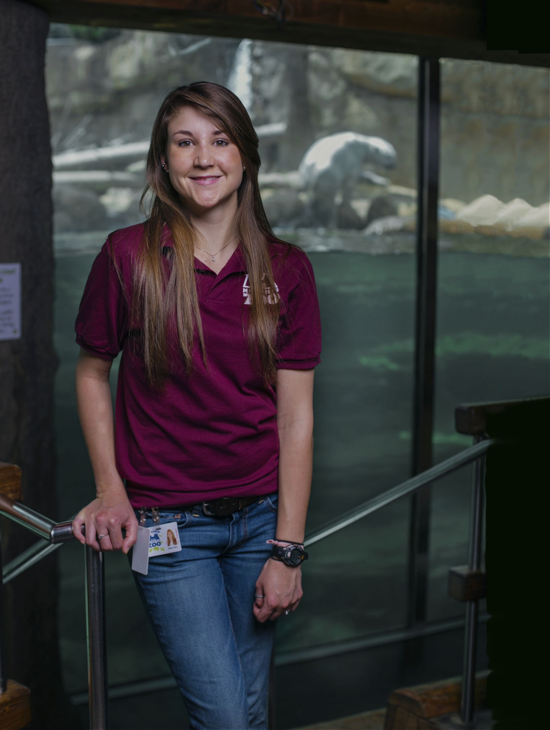 a young woman standing in front of the polar bear exhibit