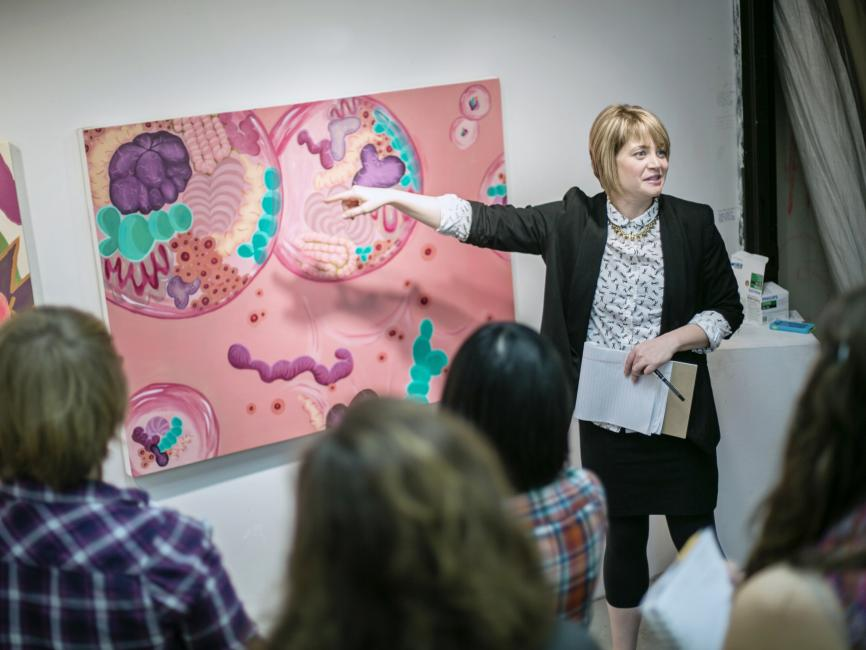 A professor points to a pink painting