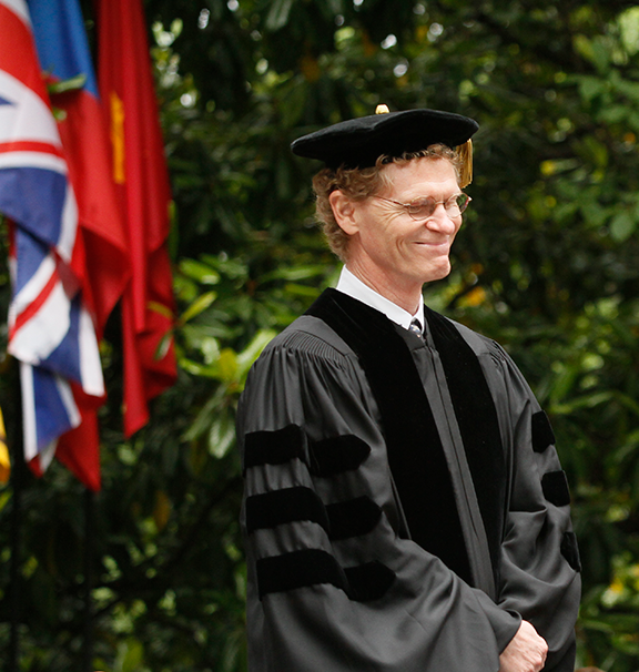 an older man with a cap and gown on smiling proudly