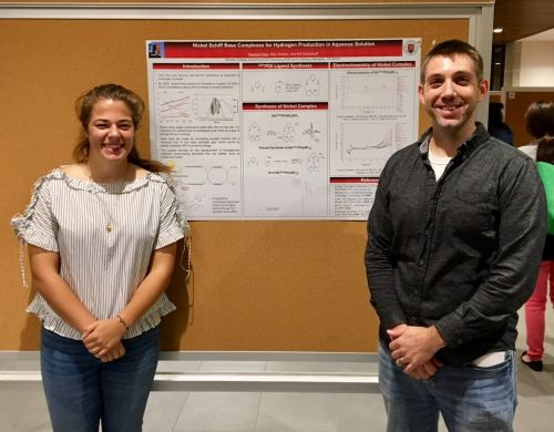 a student and a professor in front of a research poster