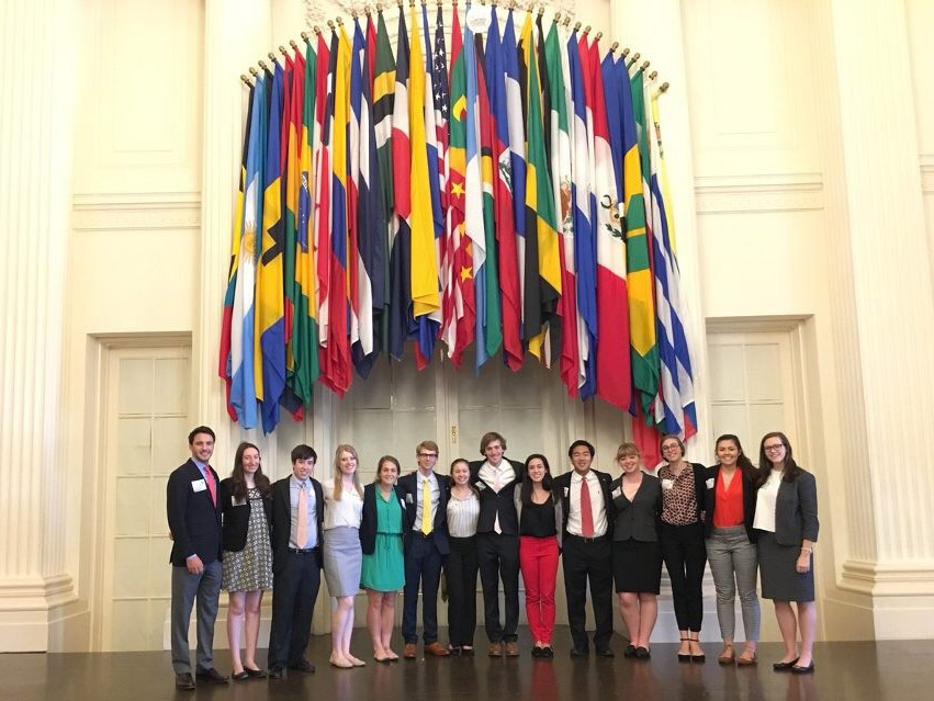 The group of young international studies program participants standing under hanging flags from various nations