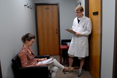 Male student in lab coat interviewing a research participant