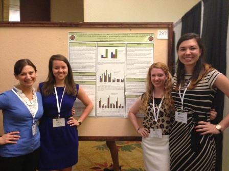 Professor with three female students presenting research on a poster board