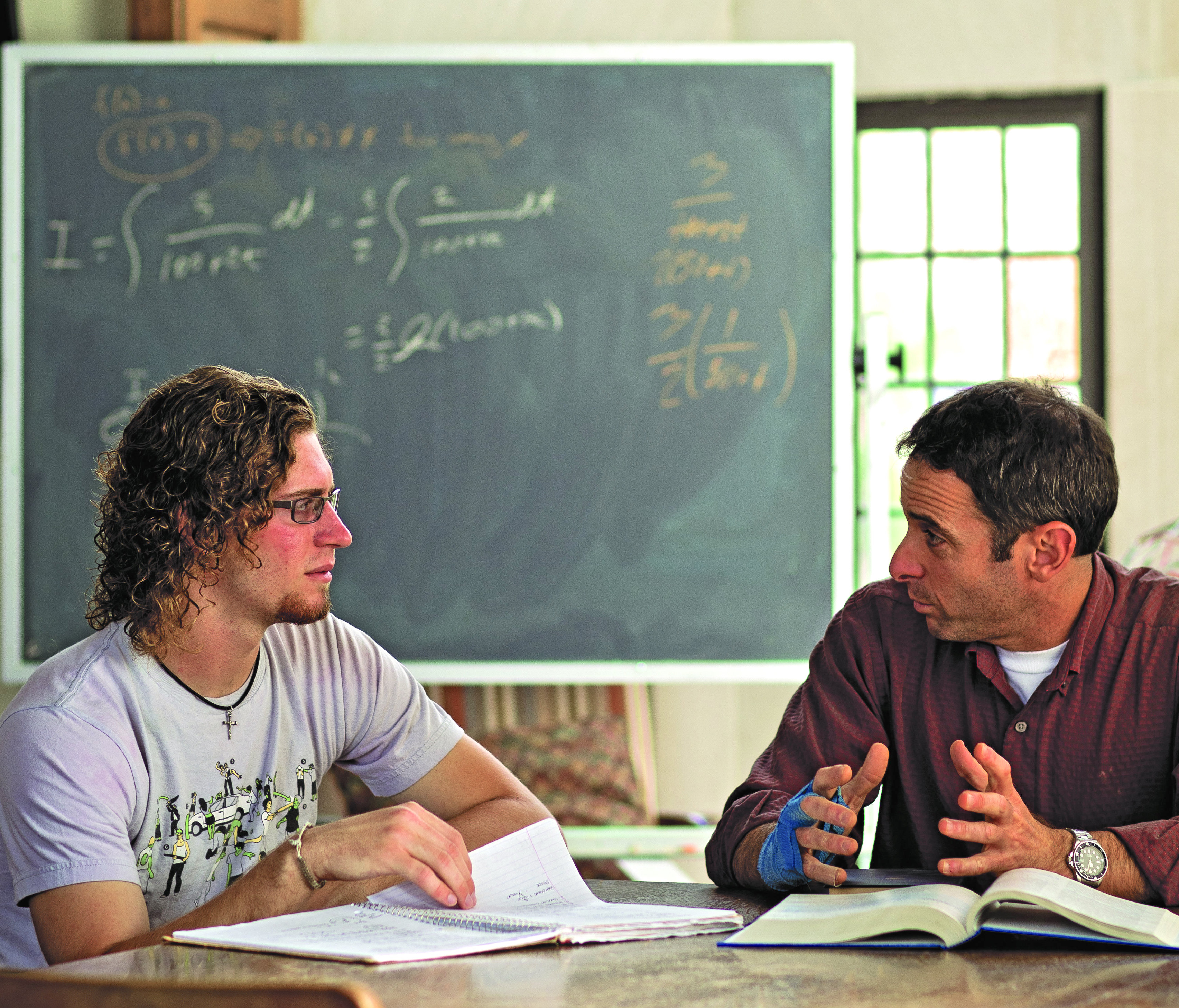 a student and professor talking in front of a chalkboard