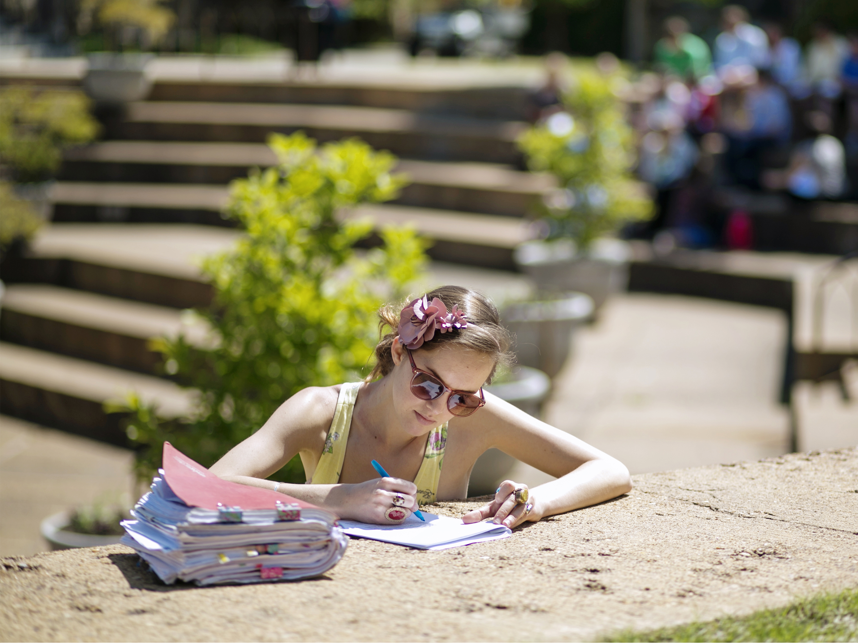 a student writing outside on some steps