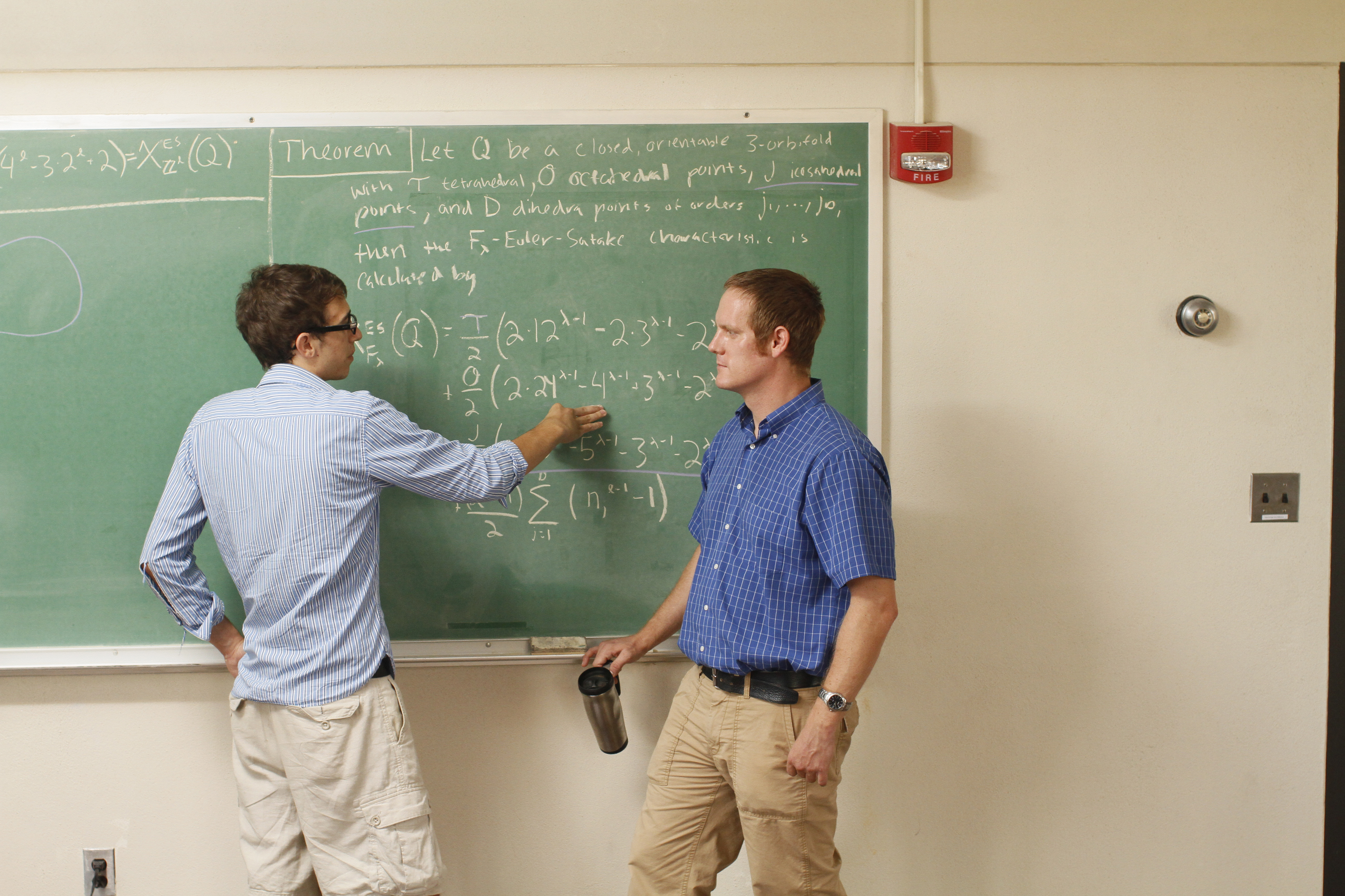 Two men work at a blackboard.