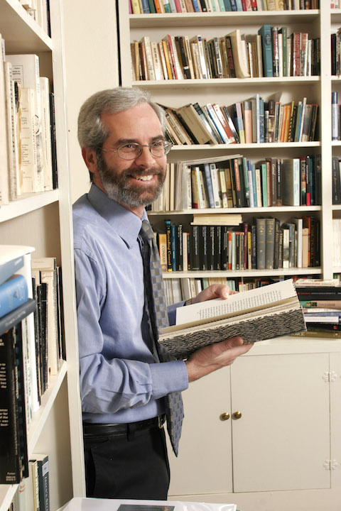 A man leans against a bookshelf