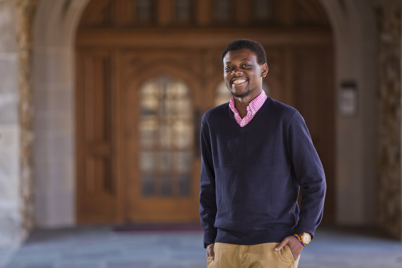 an african american man smiles under a gothic archway in a casual sweater
