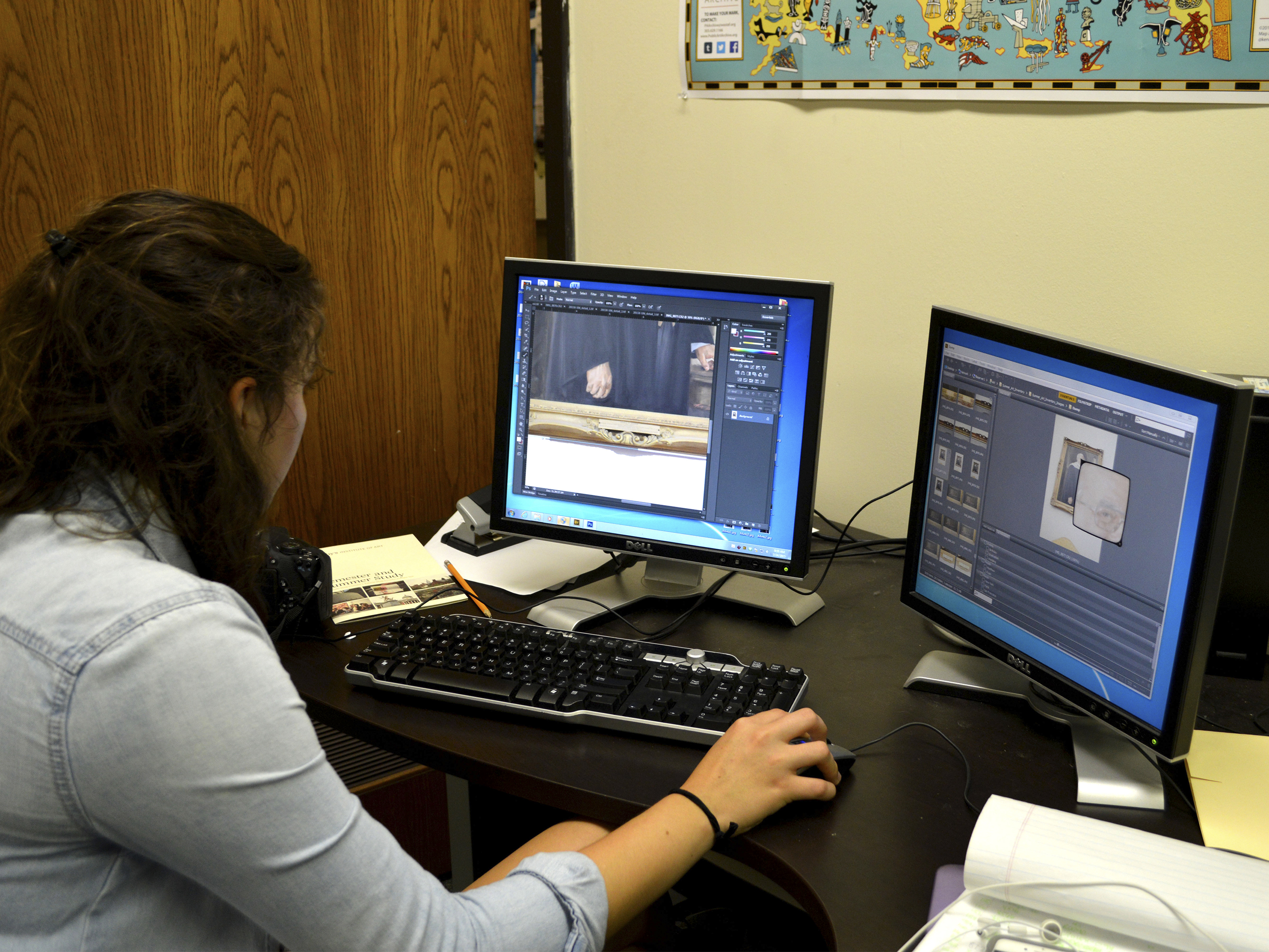A dark haired young woman works at a computer with two screens