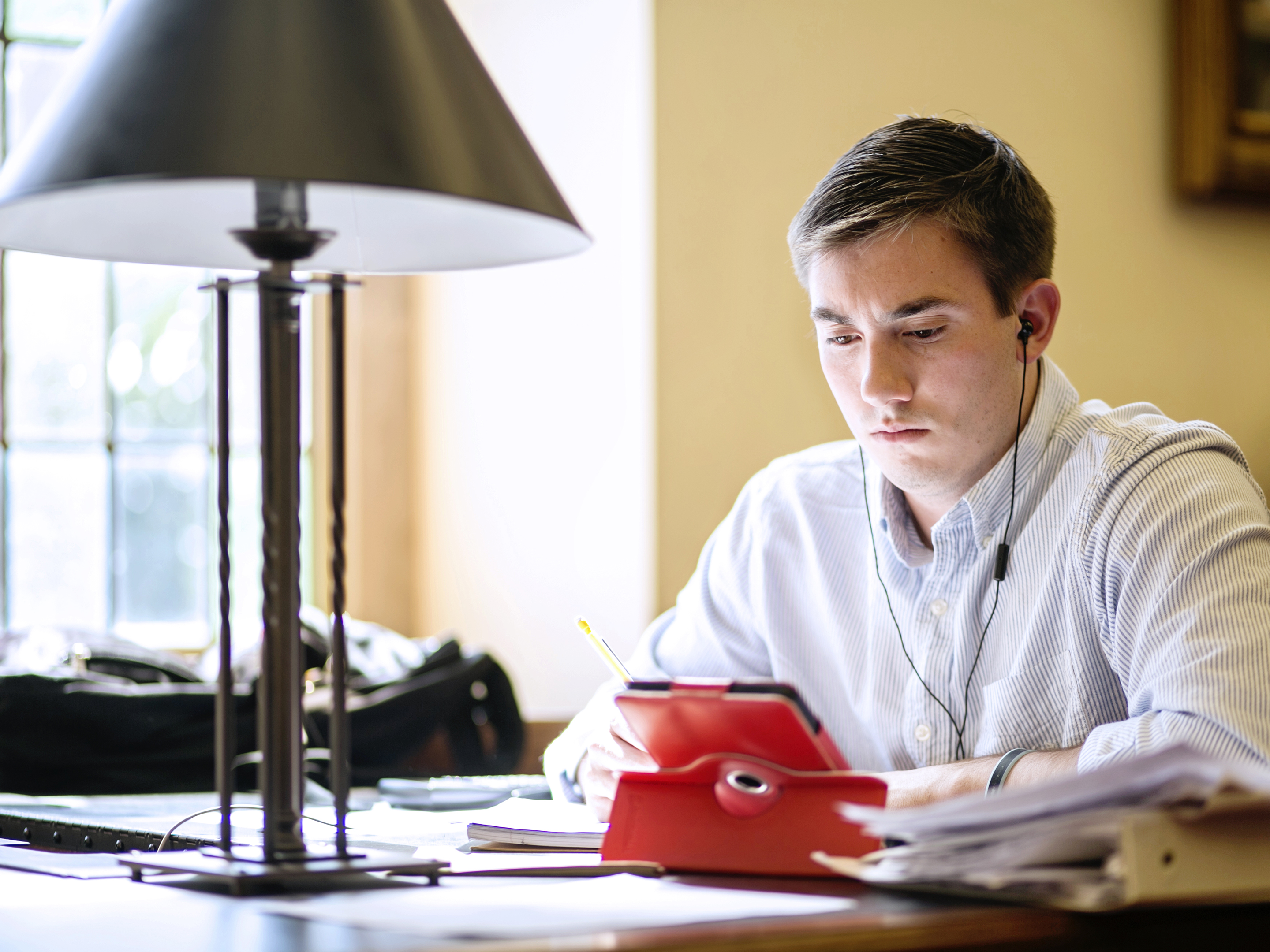 A young man with a tablet in a bright red leather case sits studying at a library table.