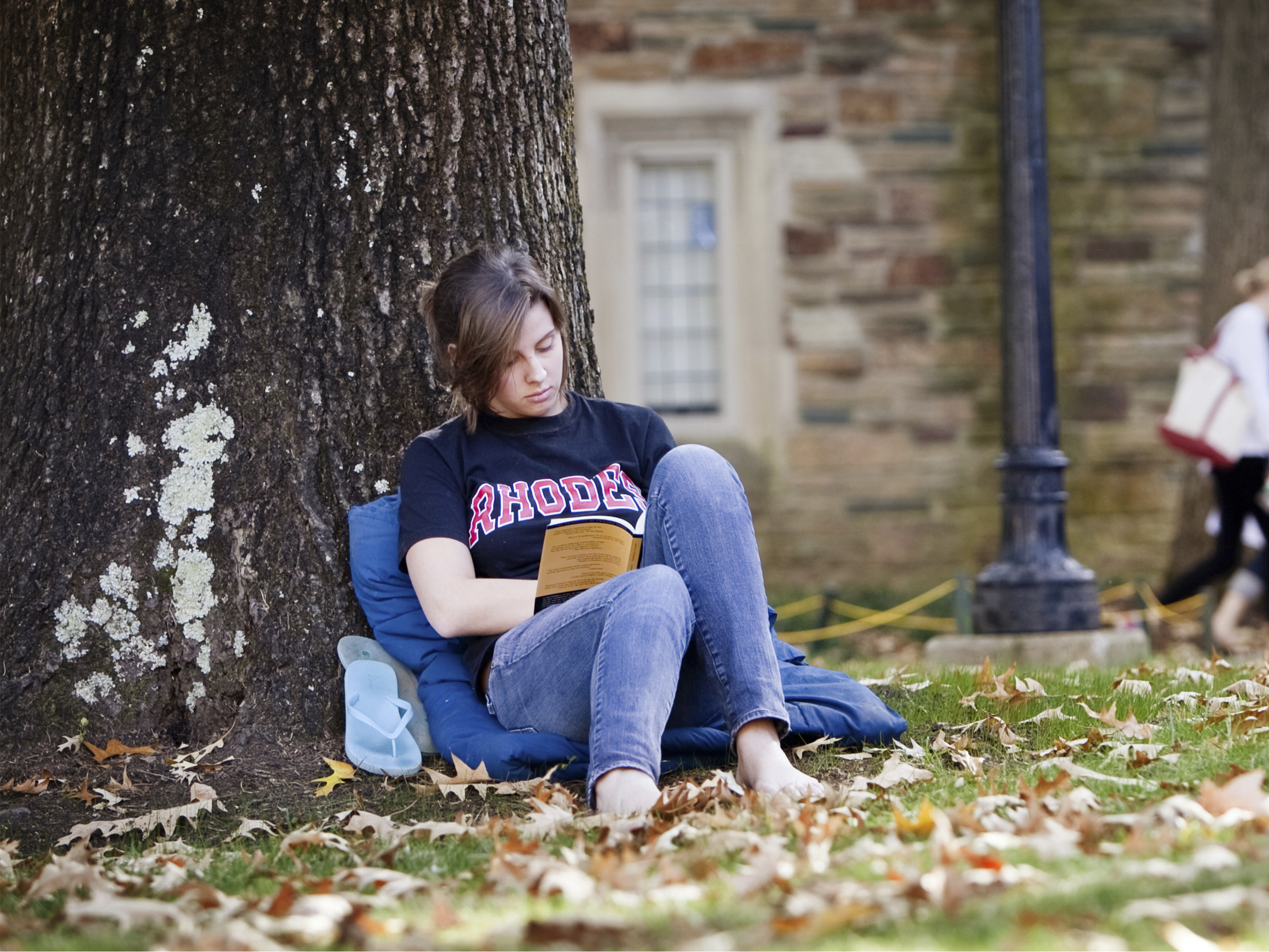 A barefoot young woman in a Rhodes tshirt and jeans sits leaning against a tree reading a book.