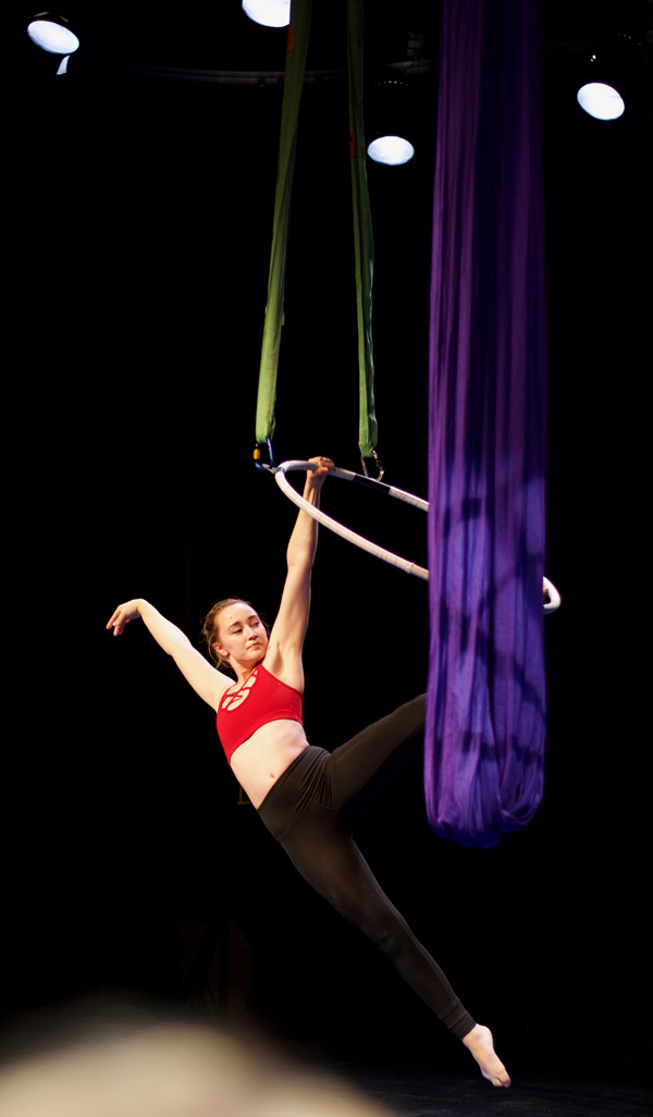 A female gracefully holding in-air arabesque on a dangling metal hoop