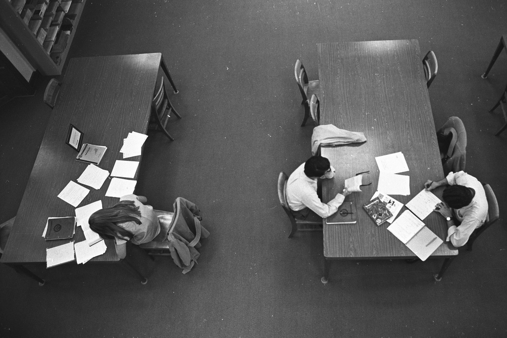 A black and white photo of students studying at separate tables, as seen from above.