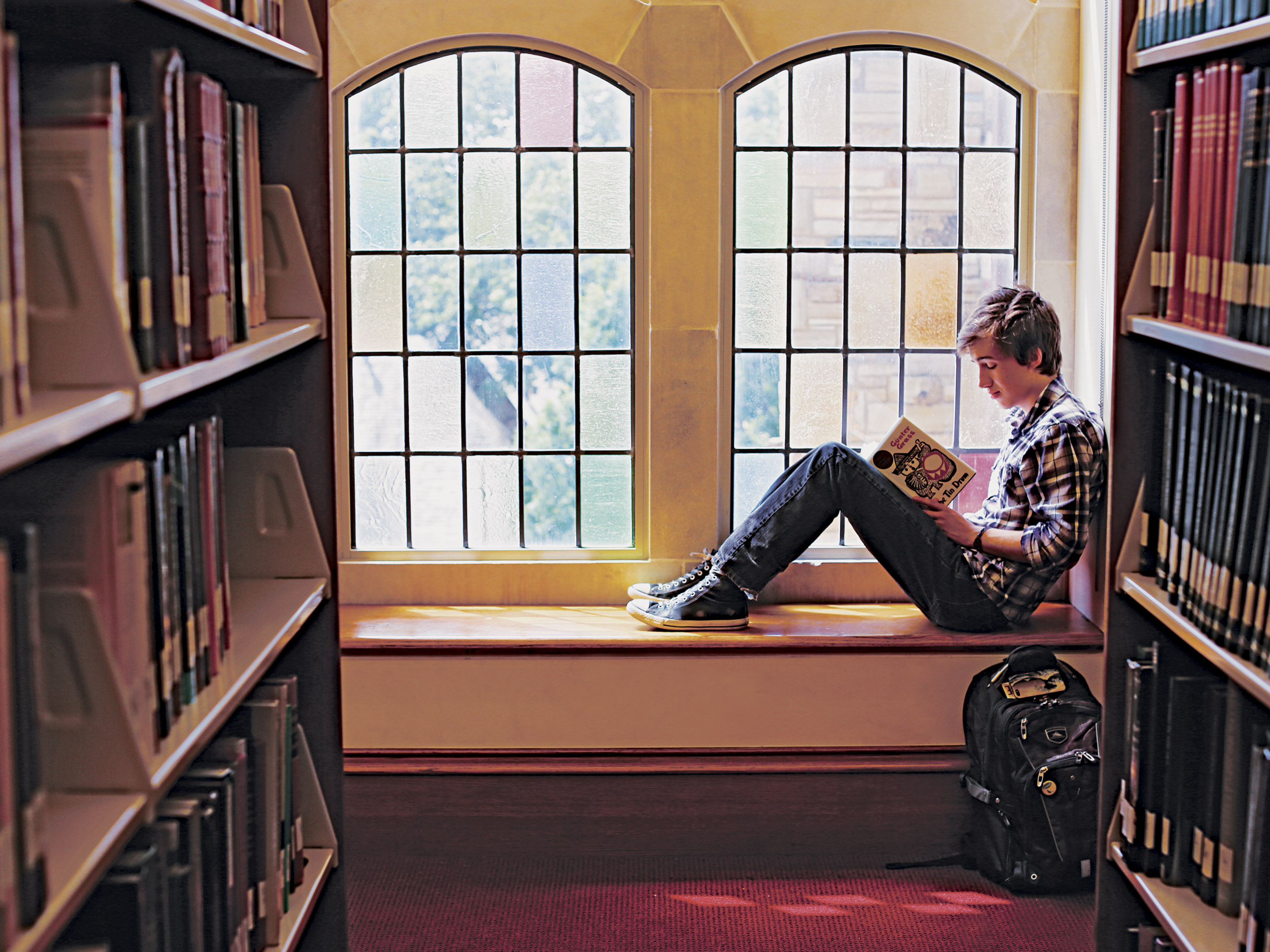 student reading a book in front of a window