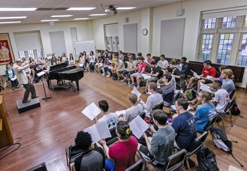 a group of students holding sheet music are sitting in a semi-circle facing a piano