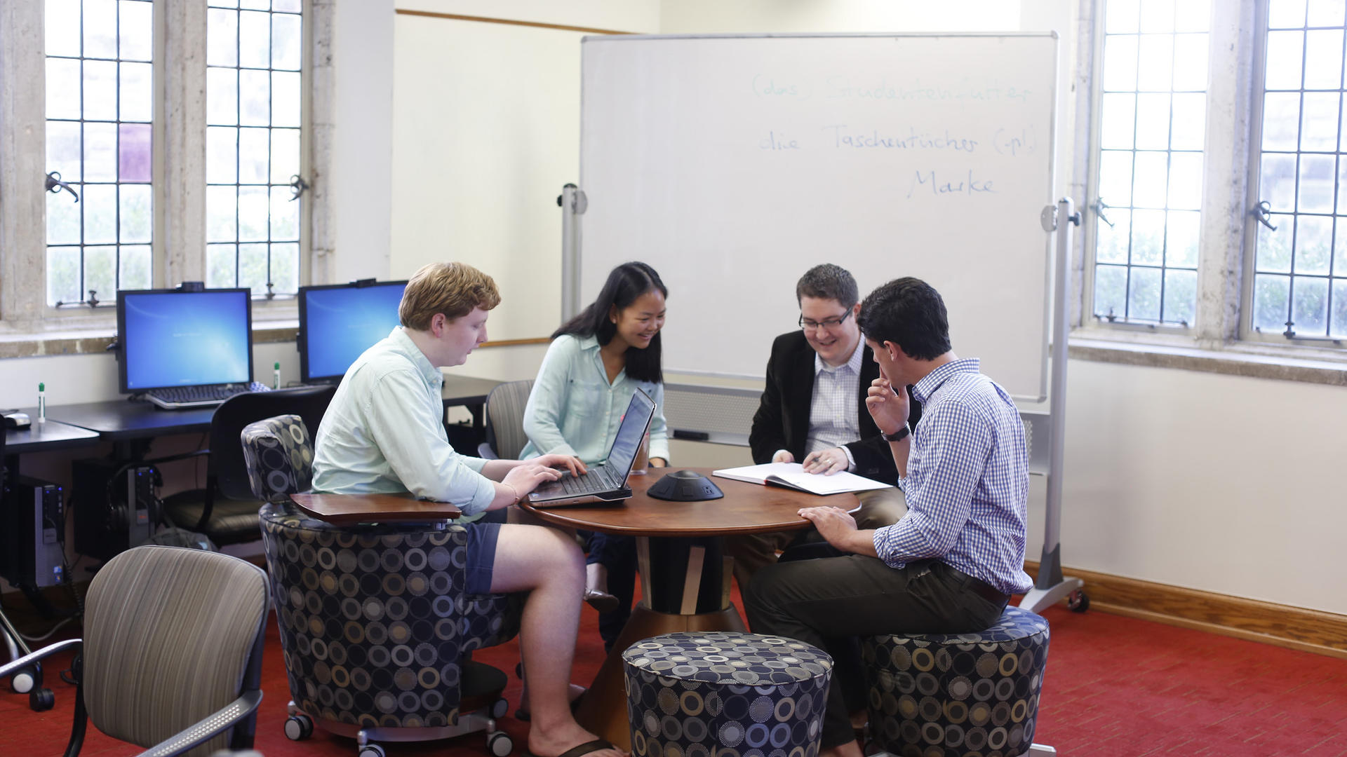 A group of students meet around a small round table.