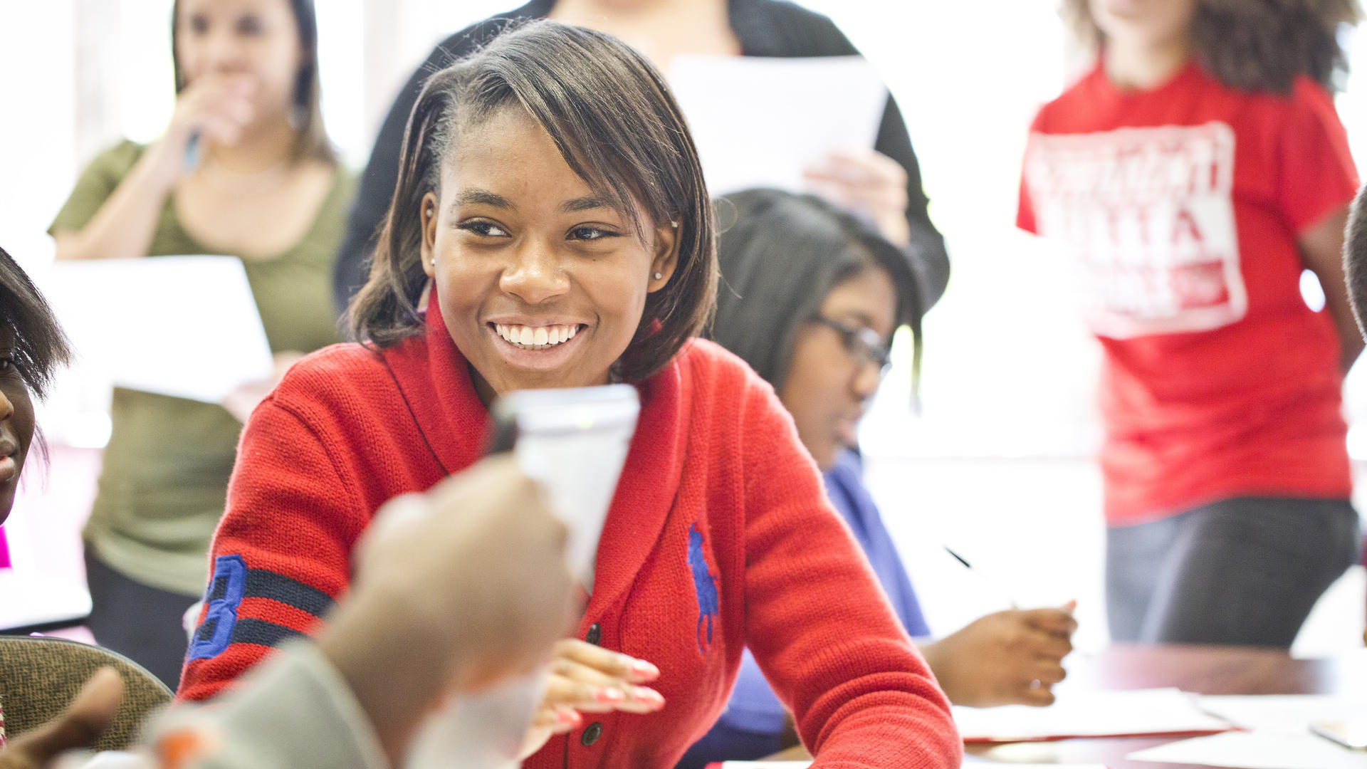 Student in red sweater sitting at a table, smiling