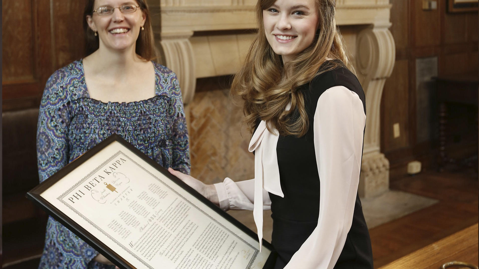 a student holds a Phi Beta Kappa certificate while a professor looks on