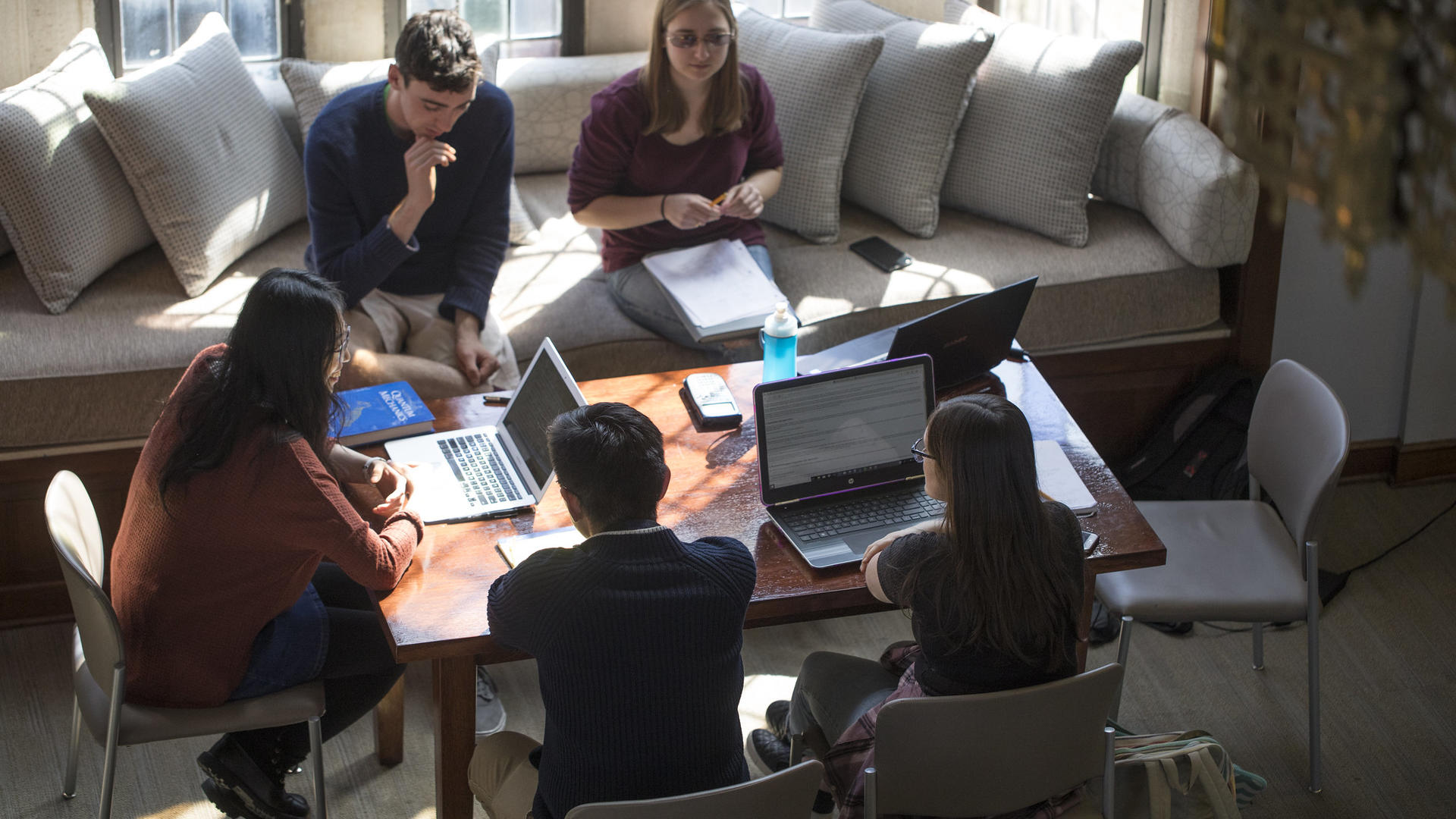 students study around a table in the math library