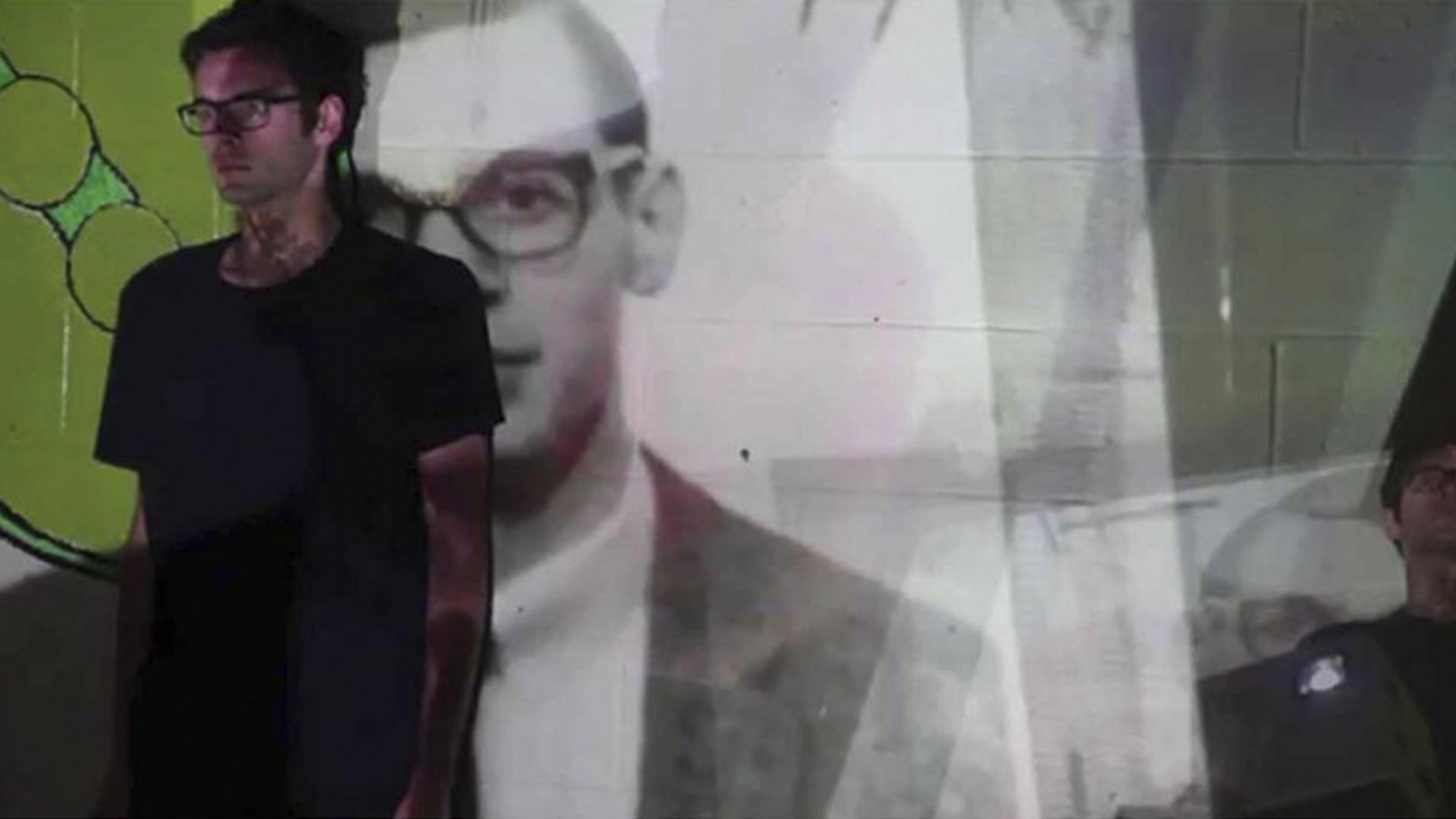 A young male student stands in the projections of a larger black and white portrait of himself.