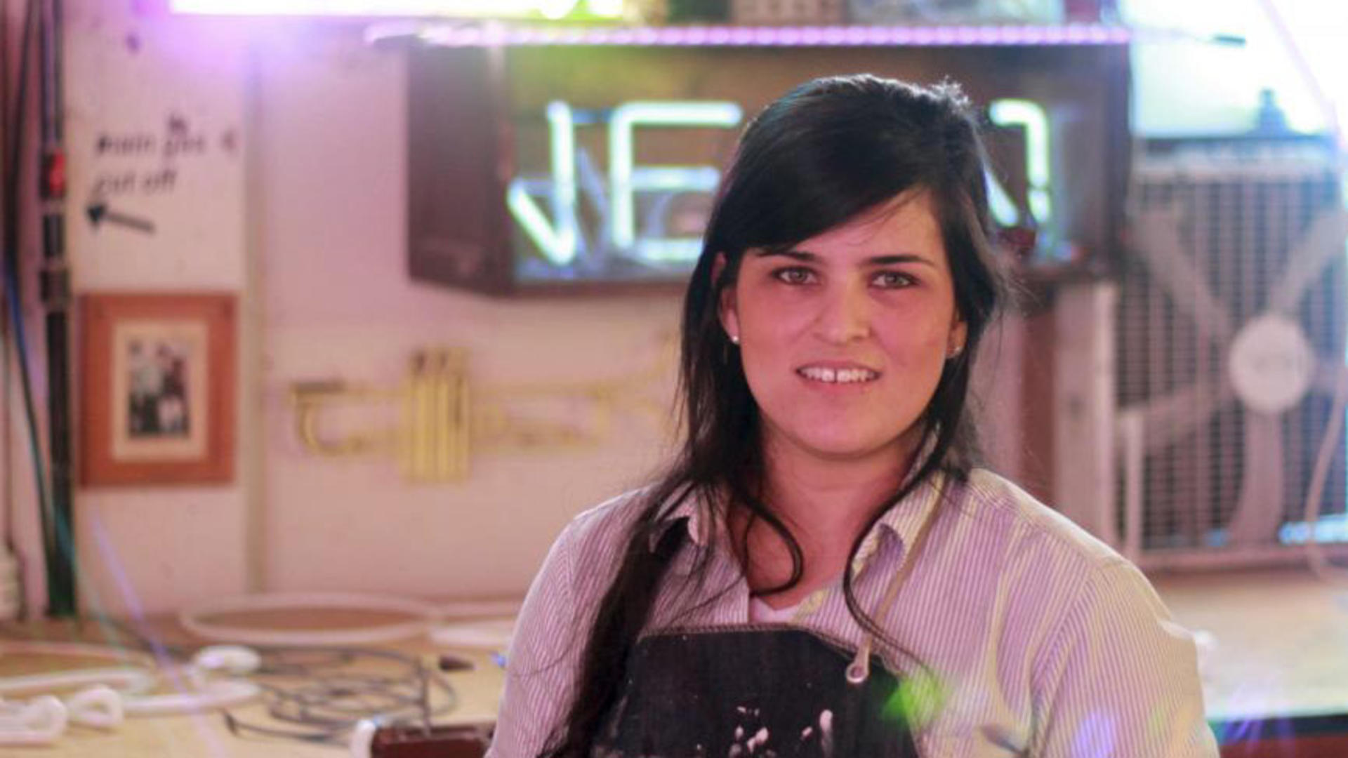 a young woman with dark hair stands in a studio in front of a neon sign