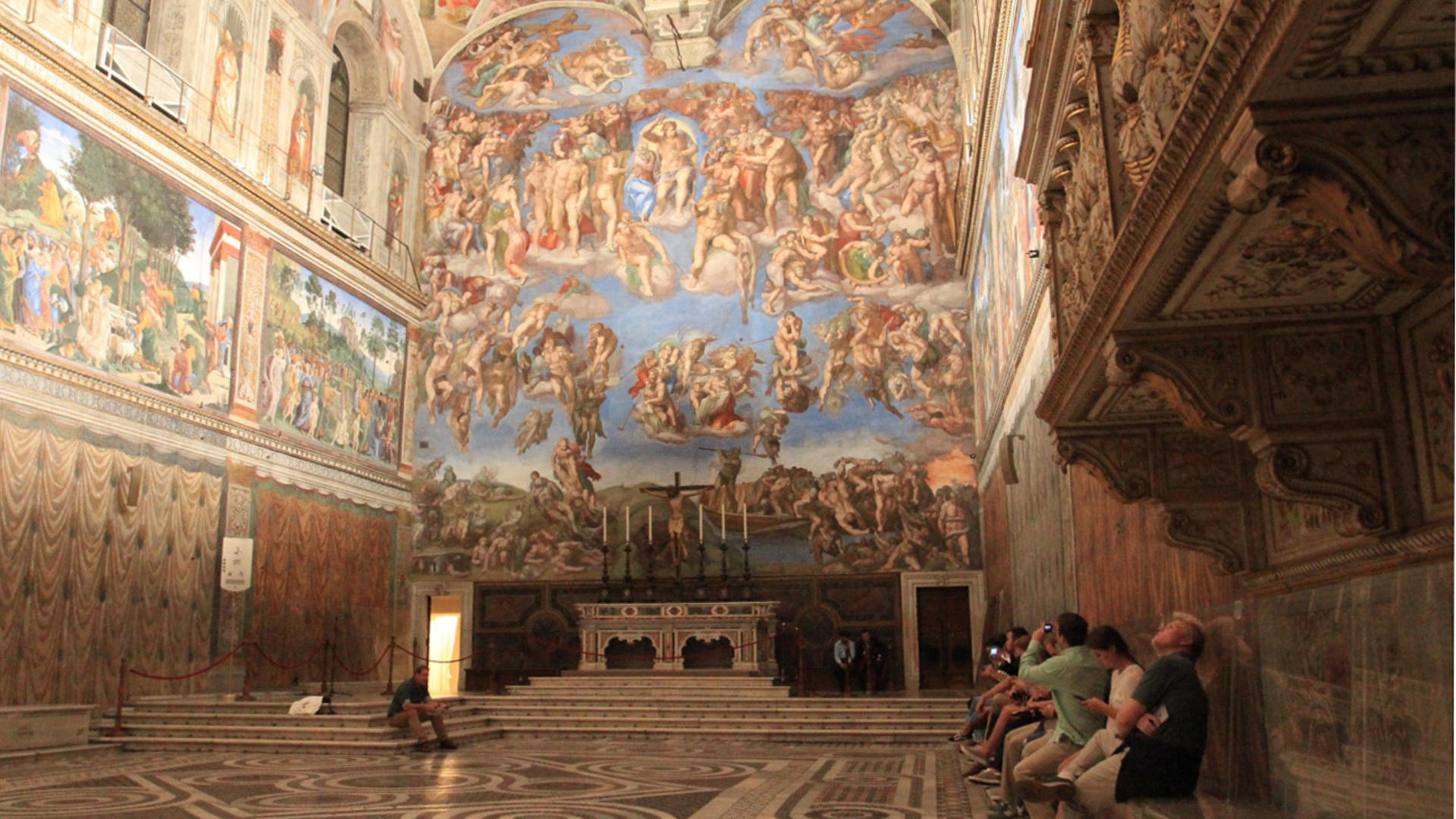 students sit on a bench and look at art in a cathedral