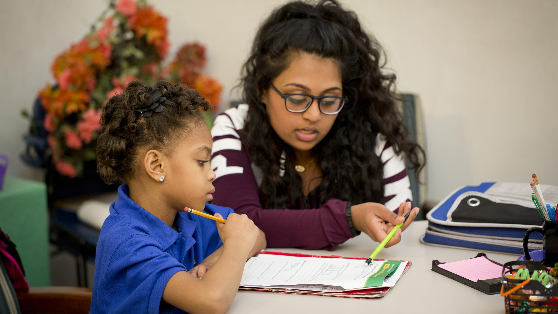 a young woman helps a young girl with her homework